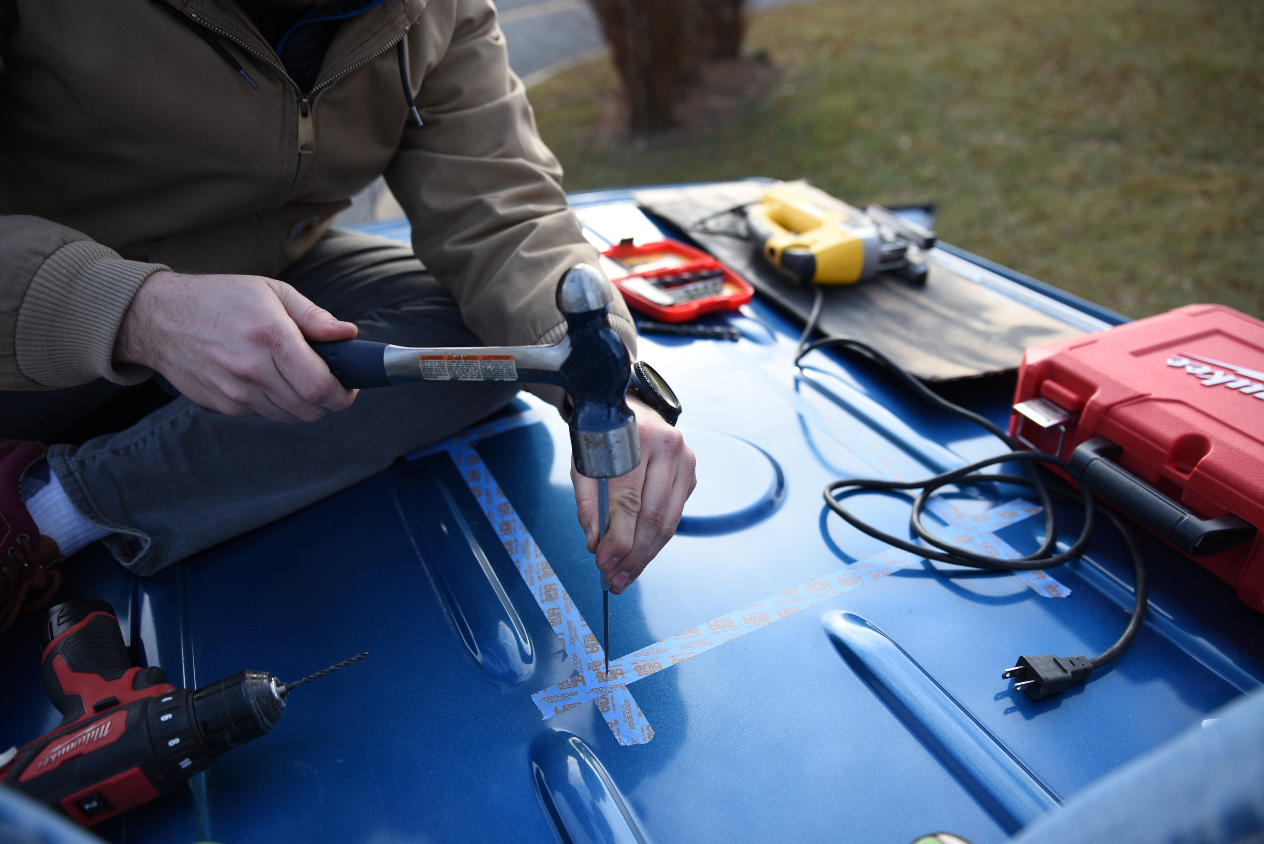 Ian uses a hammer and awl to make an indentation to allow the drill bit to gain purchase on the slippery roof of the van.