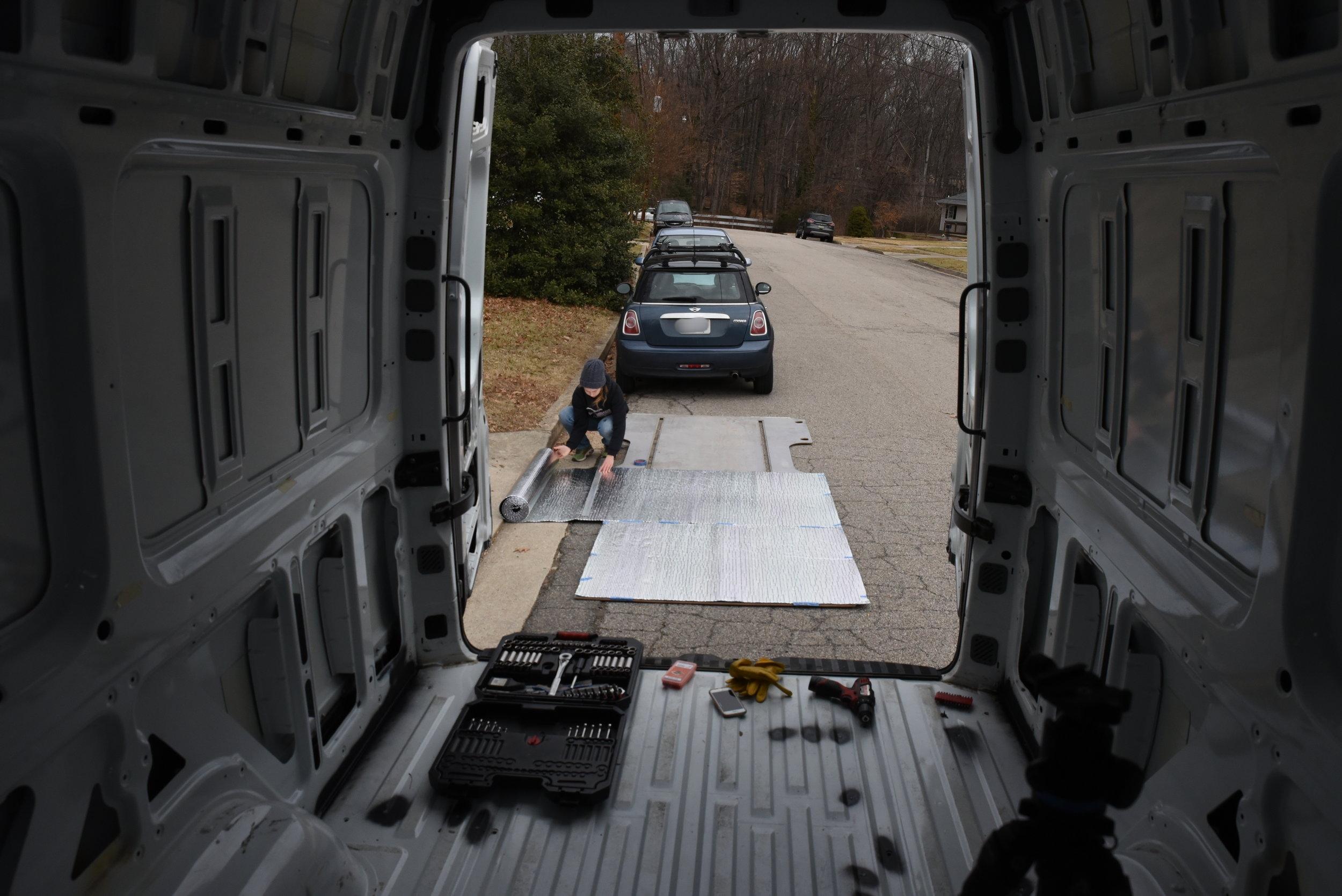 Kaylee measures the Reflectix using the van floor as a template.