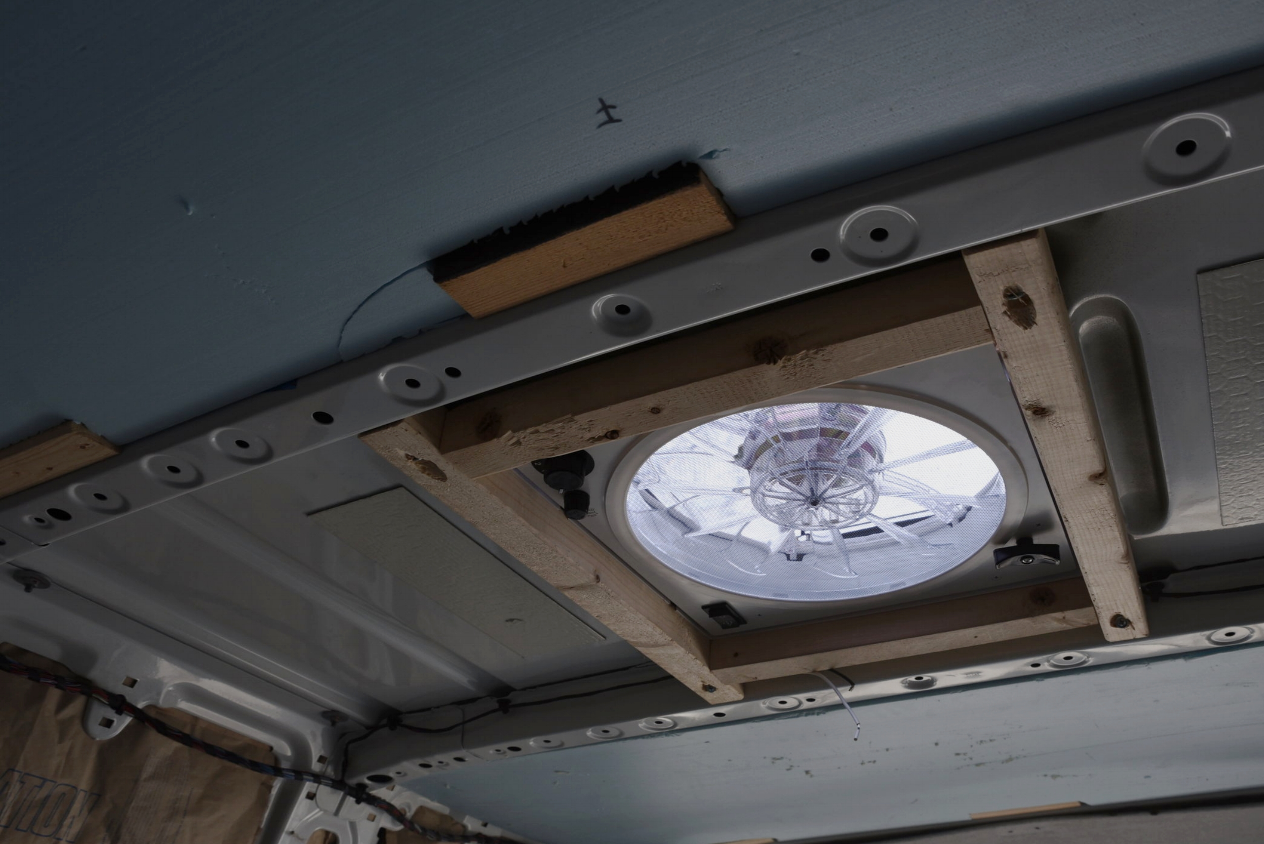 The finished fan installation in the roof of the van with the wooden frame around it.