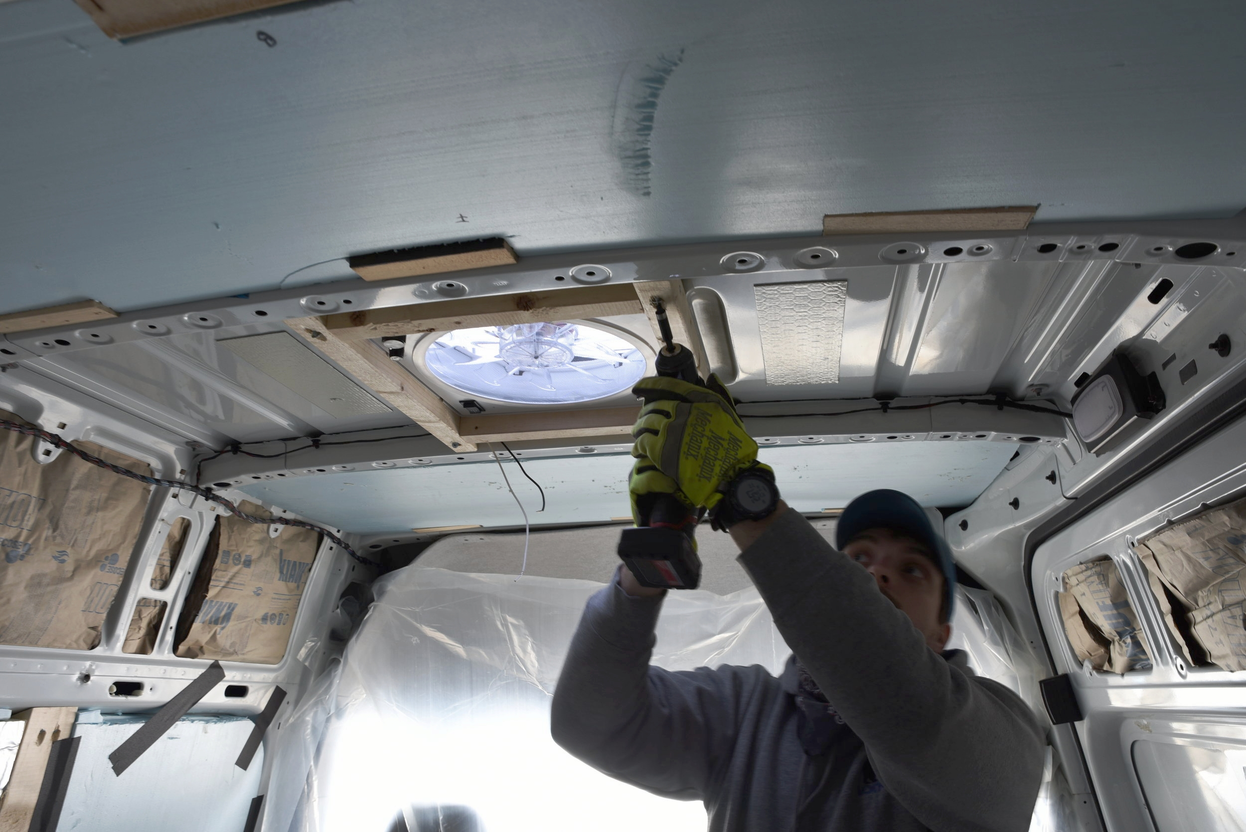 Ian screws the fan's frame into the ribs of the van roof.