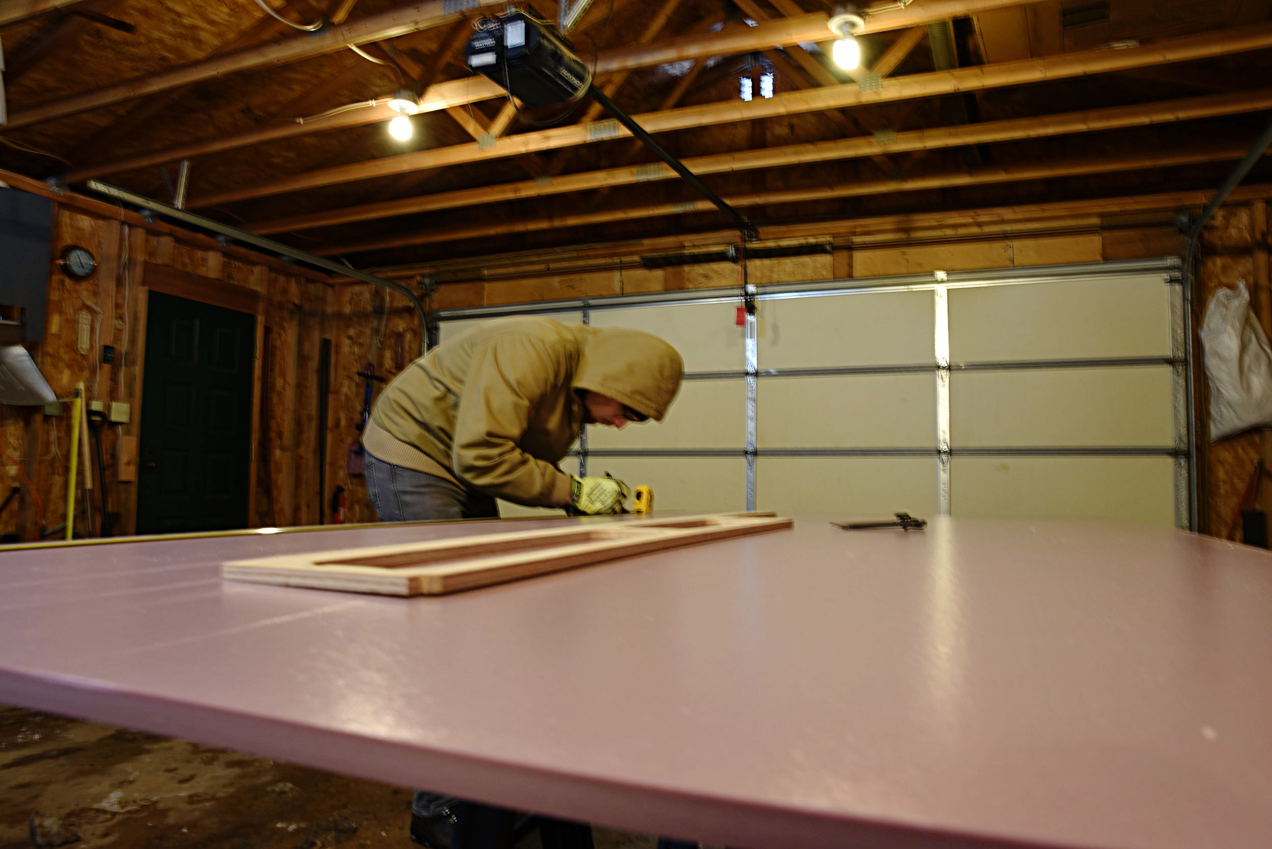Ian measures and cuts the floor insulation for our main kitchen and living space.