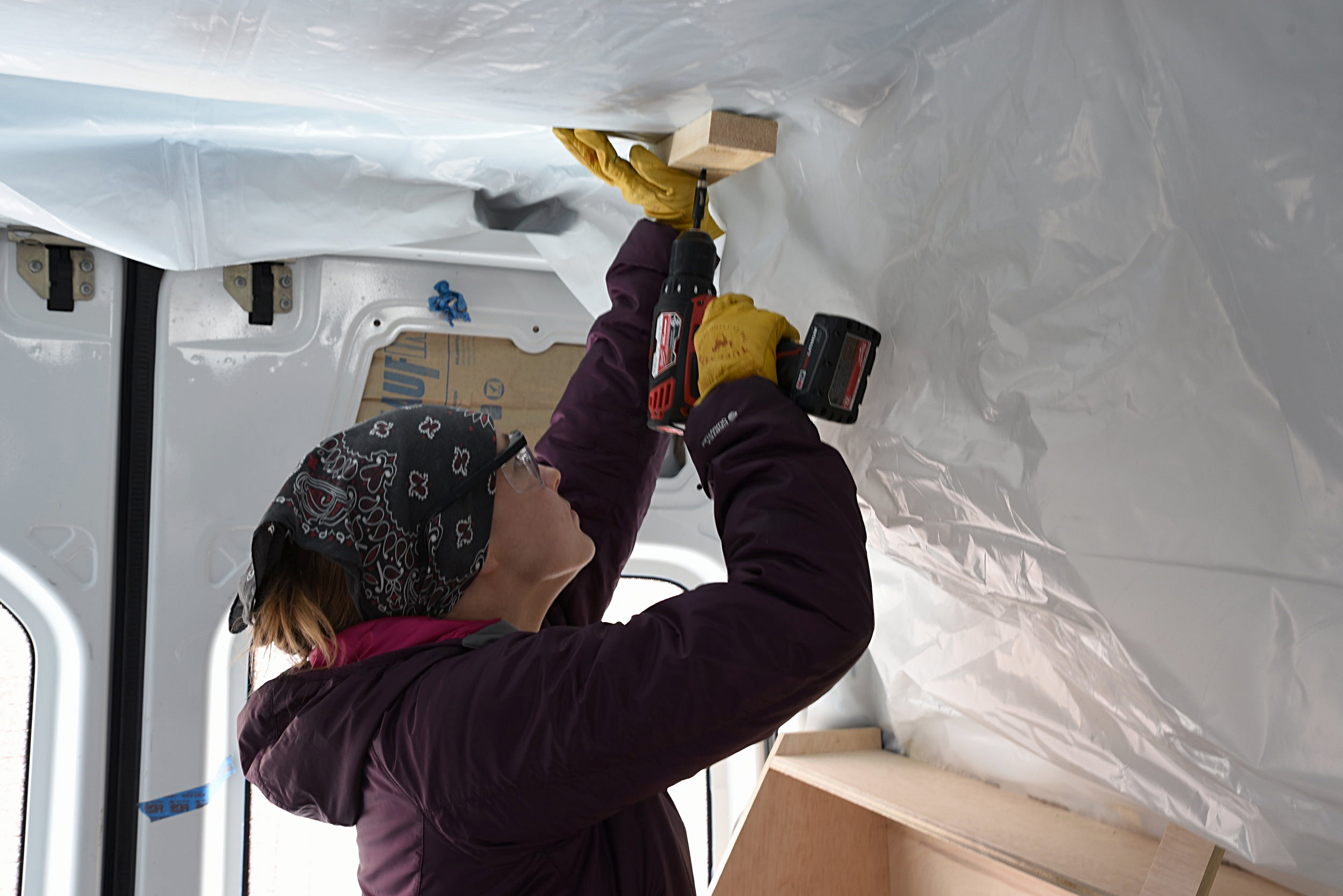 Kaylee uses some scrap wood to hold up the plastic sheeting until we are ready to install our ceiling panels.