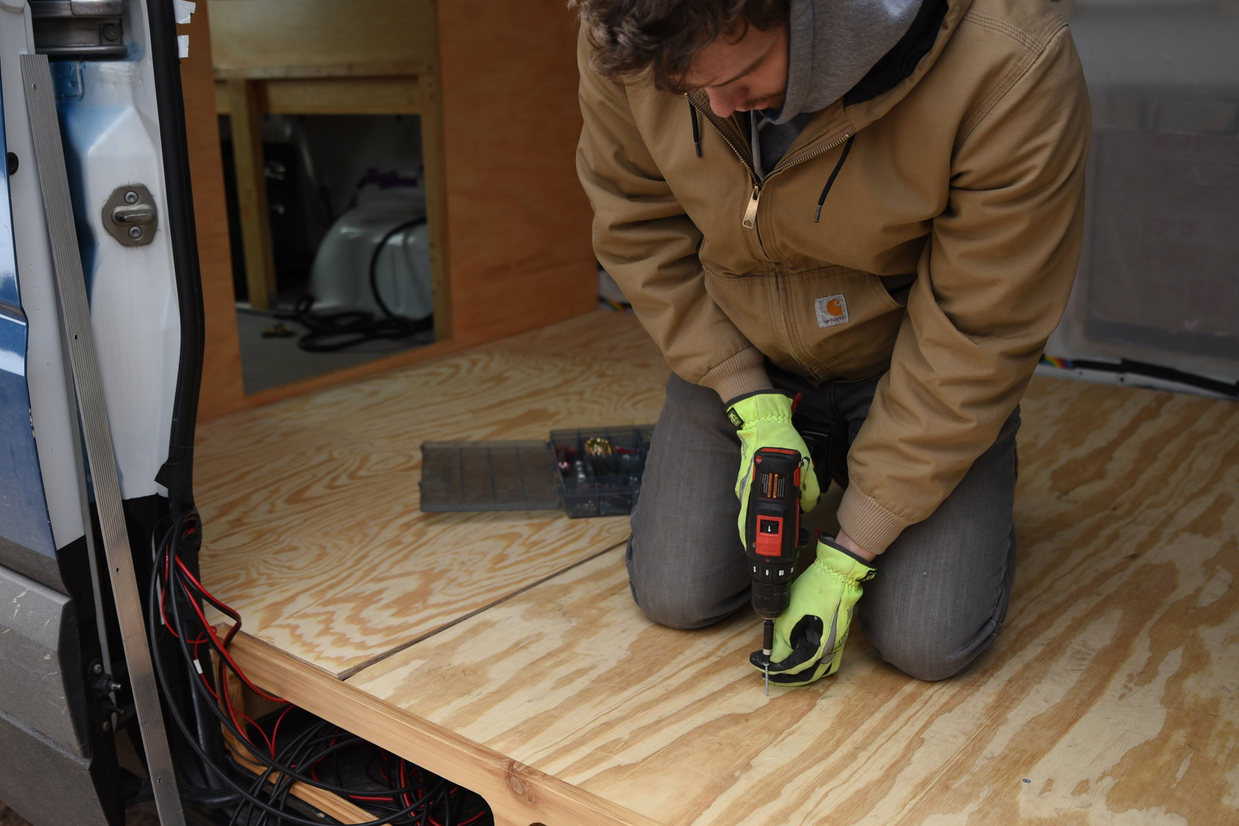 Ian screws the plywood underlayment through the foam insulation into the plywood subfloor below.