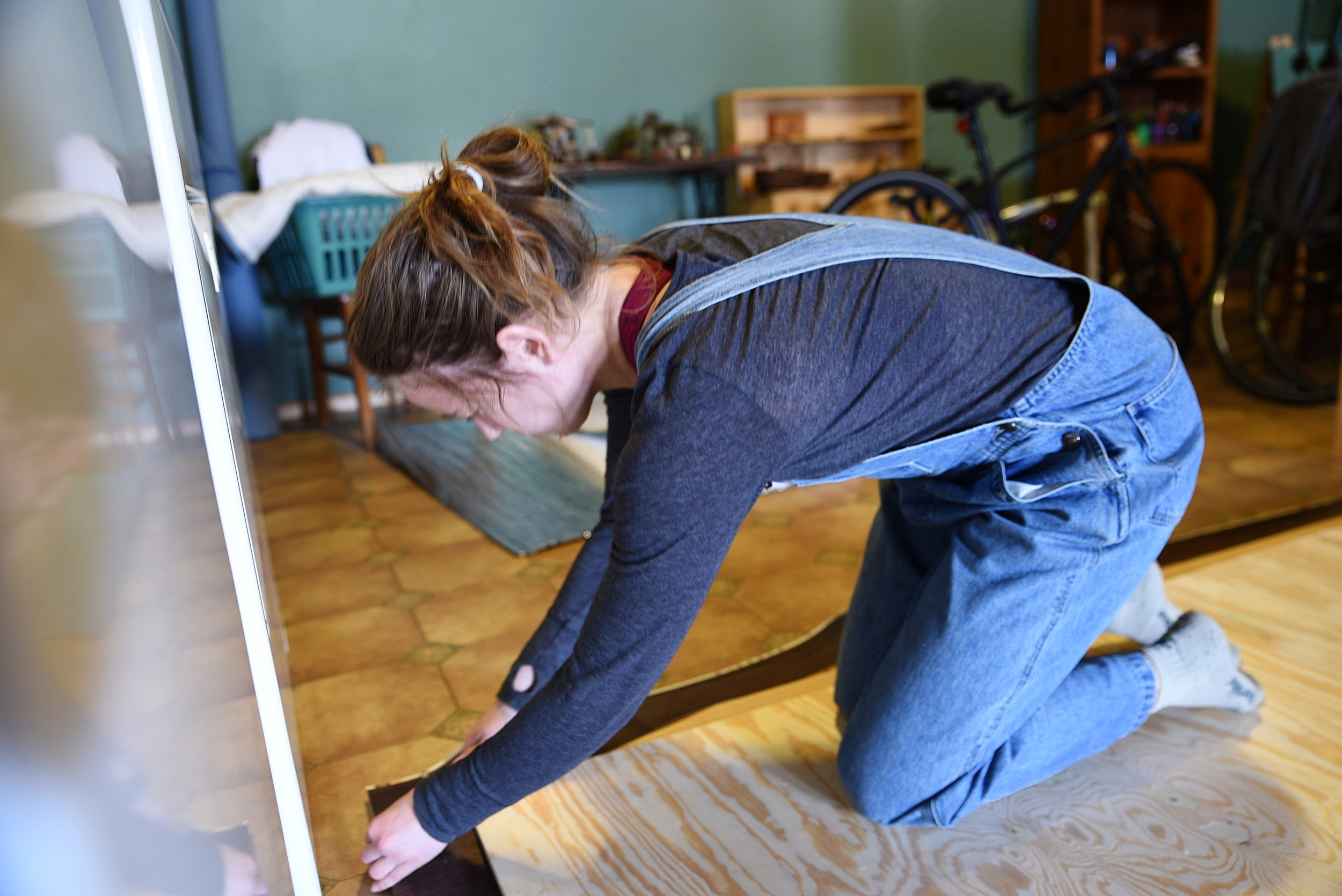 Kaylee uses a utility knife to cut the vinyl sheet flooring.