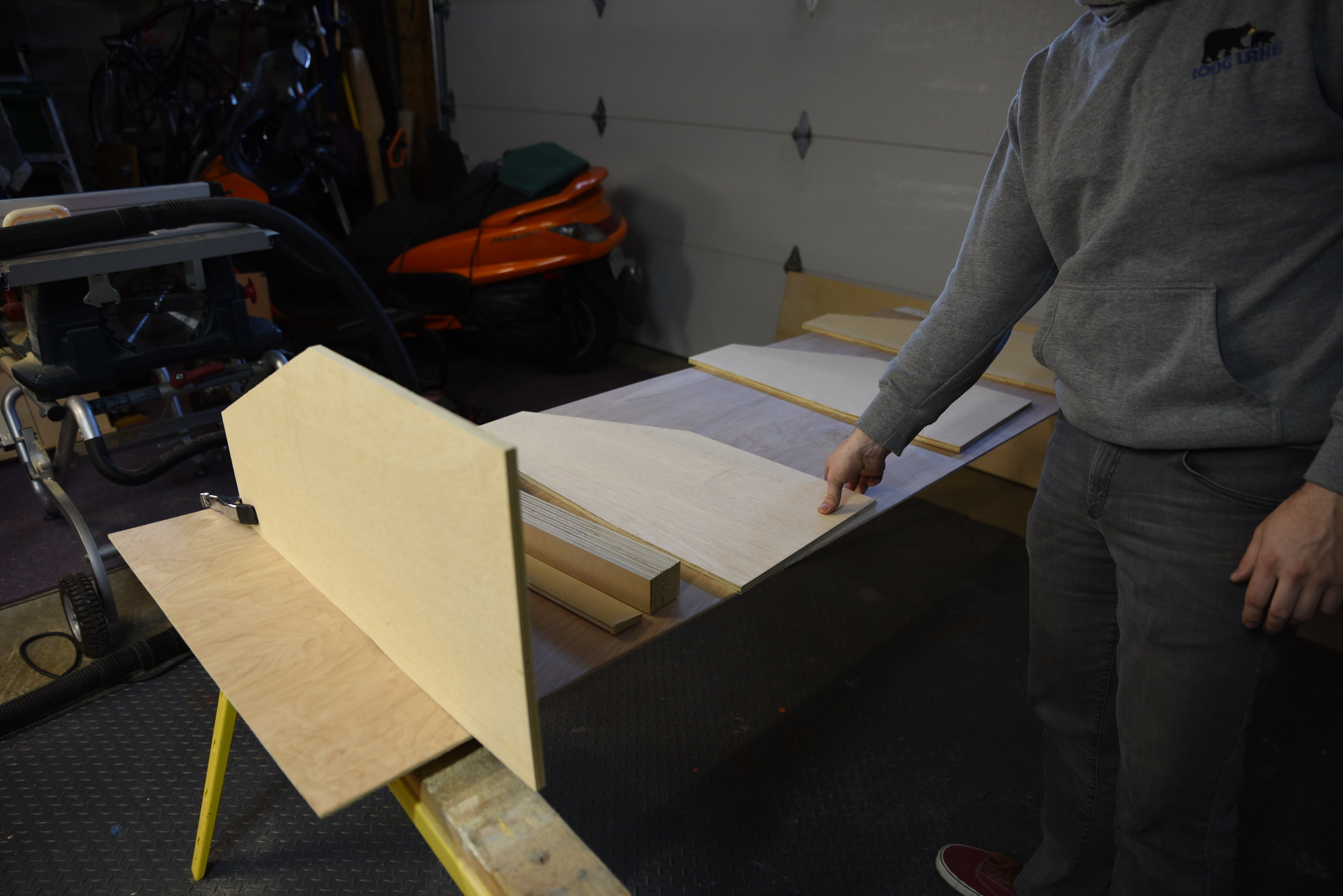 Ian lays out all of the wooden pieces of the cabinetry, while planning the best way to fasten them.