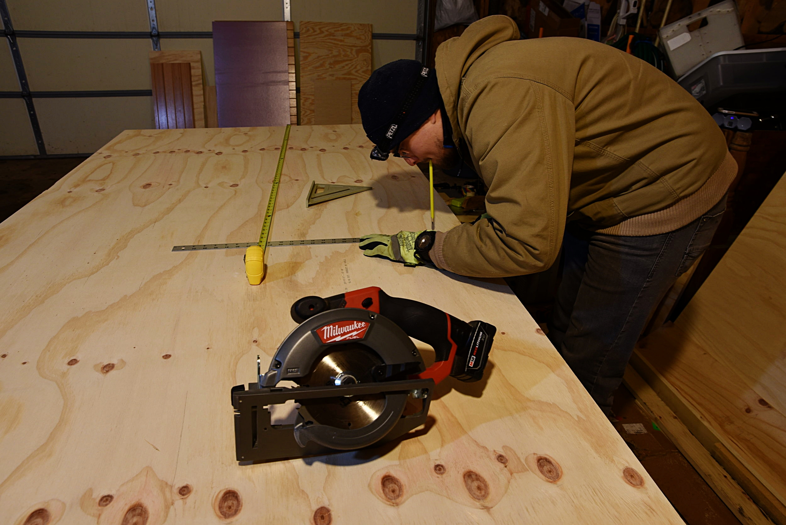 Ian carefully measures each piece of the fridge storage bench on a piece of 3/4-inch plywood.
