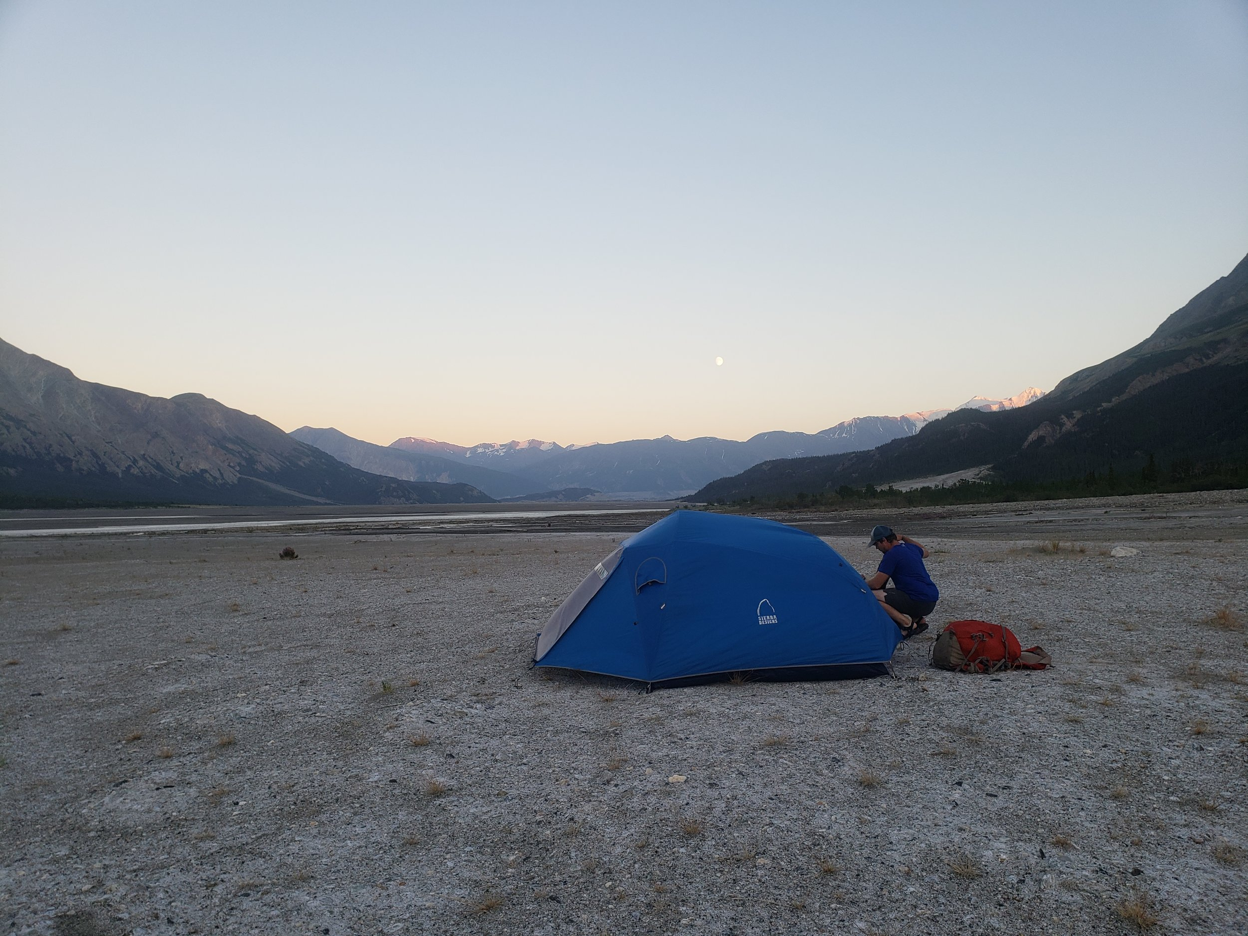 Ian gets his sleeping bag out while the moon rises over the mountains behind.