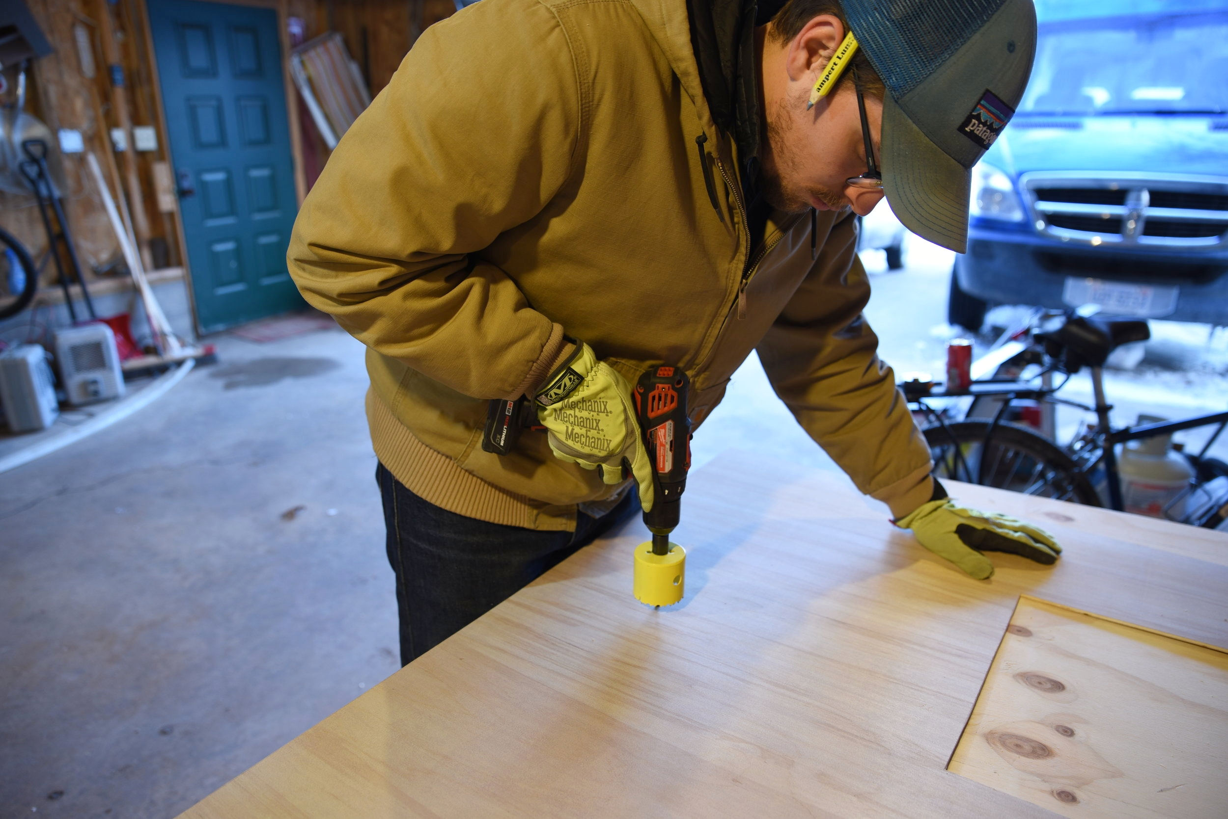 Ian uses a hole saw to cut the holes for the solar-powered, 12-volt lights.