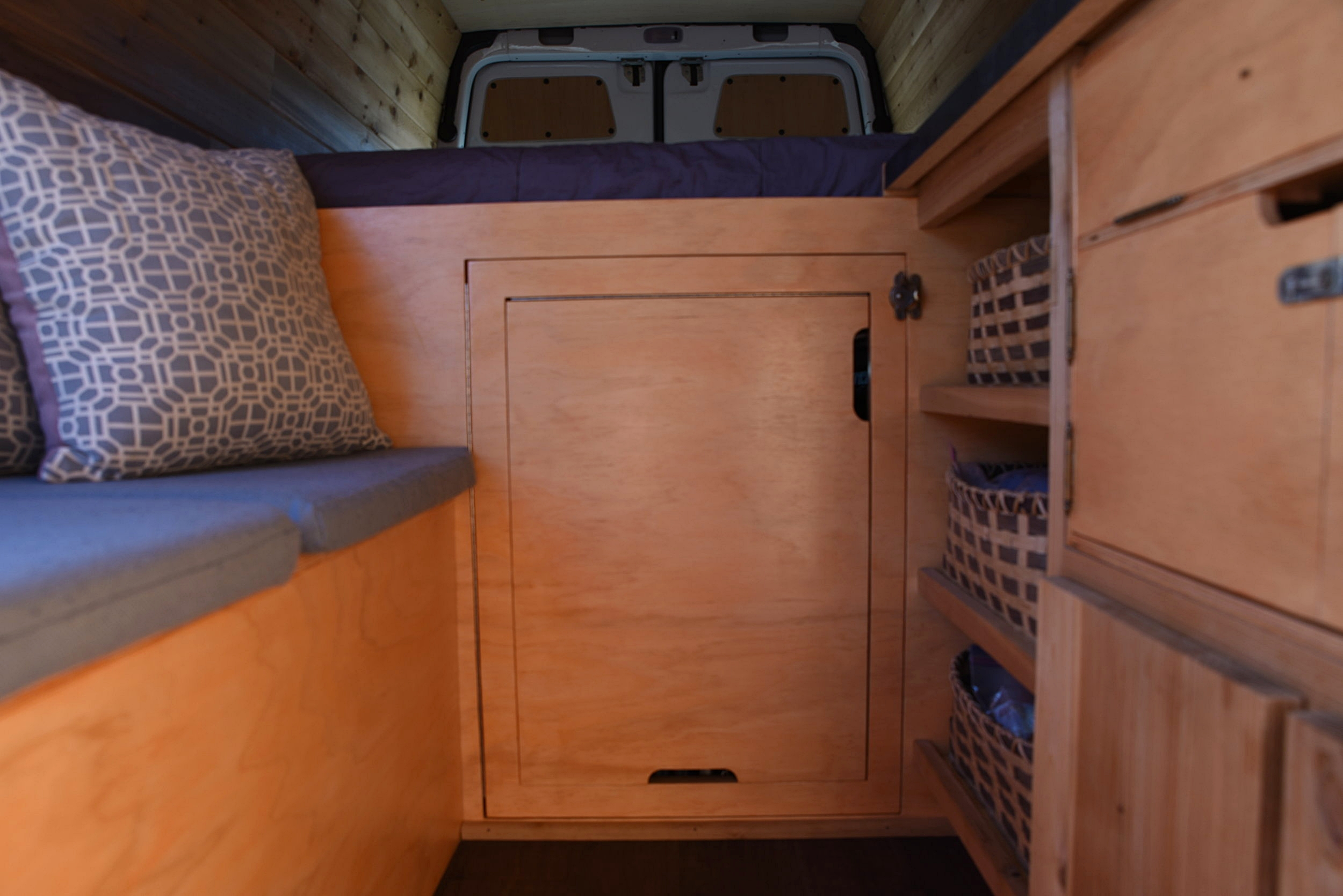 The door fits within the front of the bed platform, hinging out. The table fits within this door, hinging up.