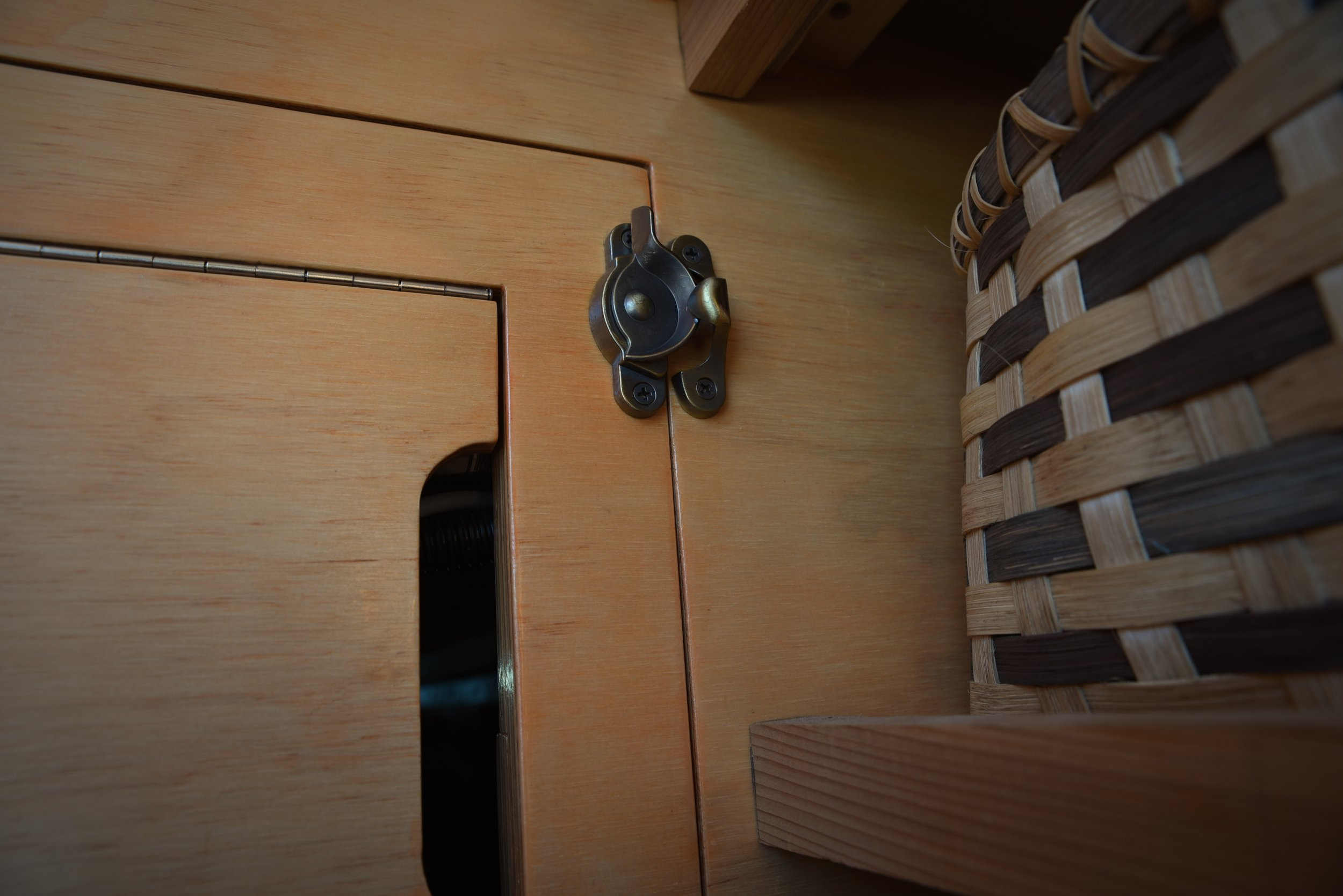 A sash lock (usually used on windows) is a stylish and latch for keeping our giant cabinet door closed while we drive, and also while we use the table.