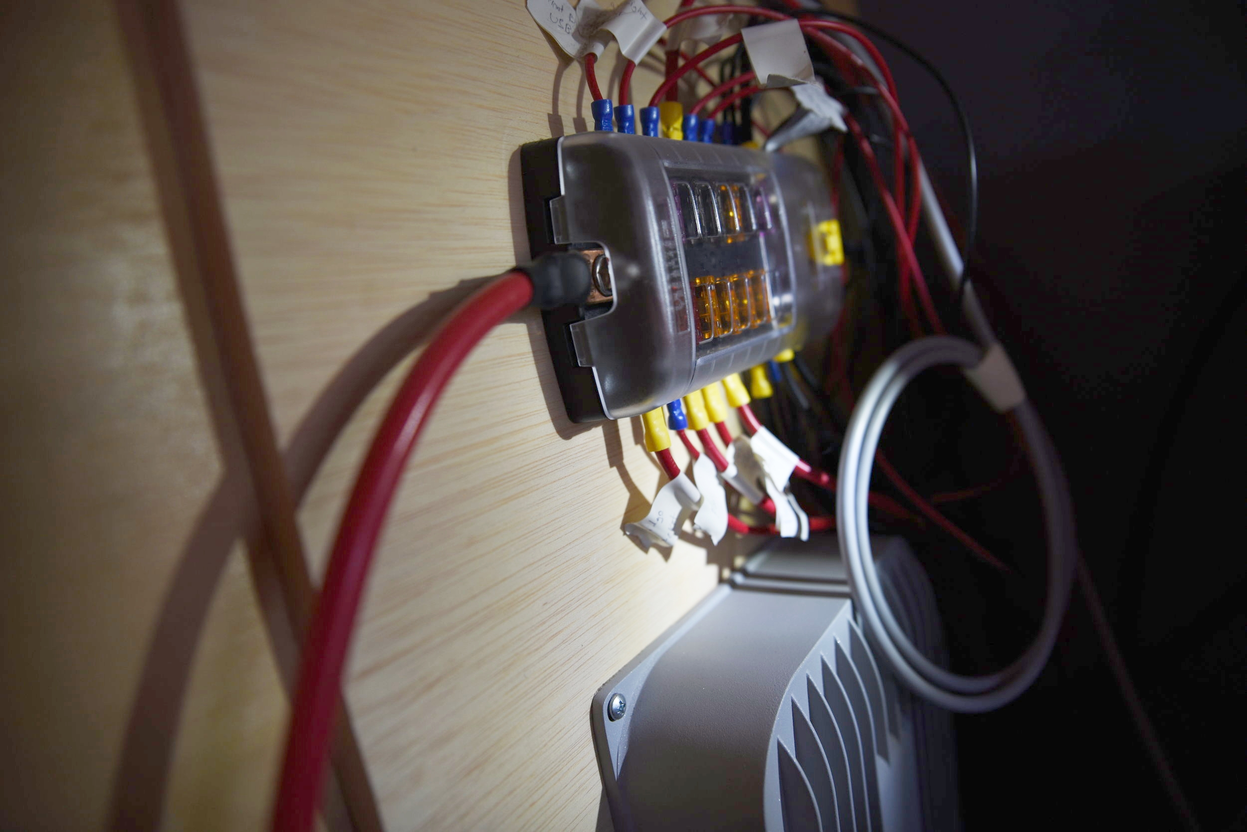The fuse box and solar charge controller are mounted to the back of the bed platform's front.