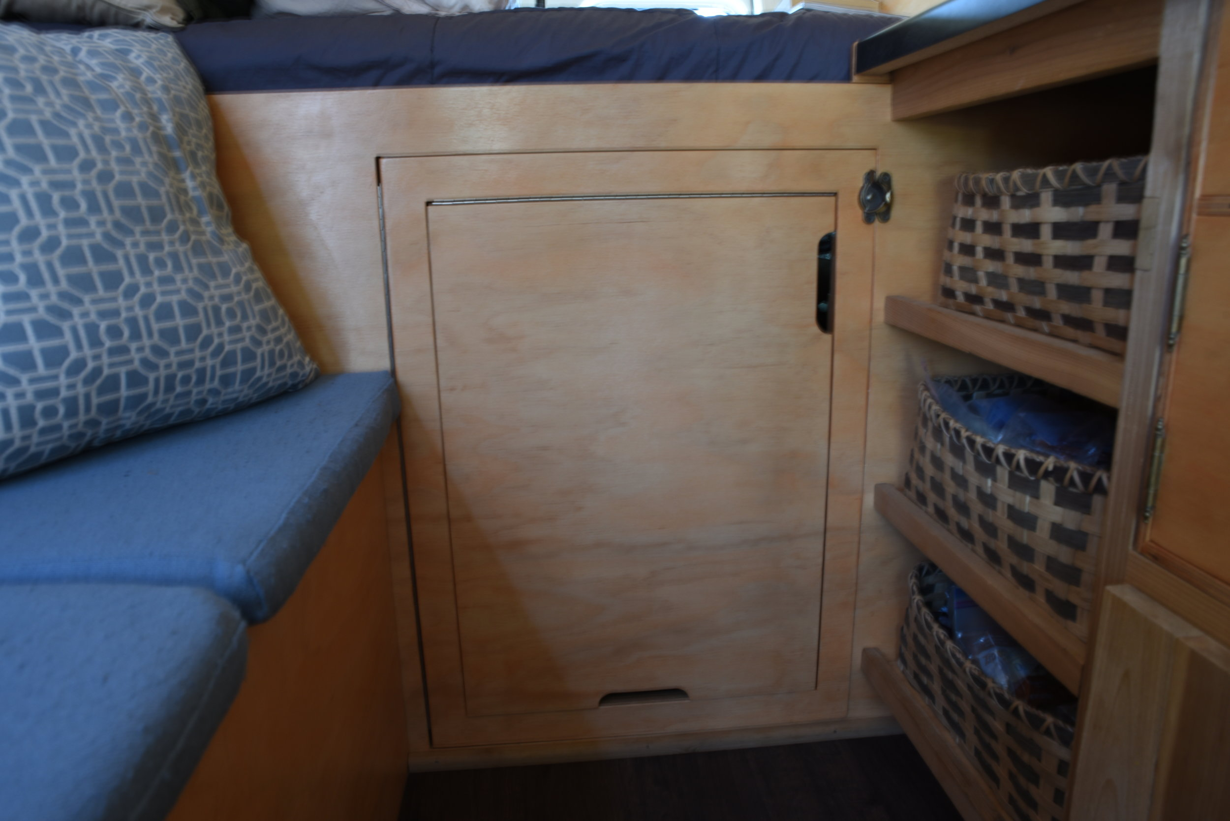 The front of the bed is finished with plywood with a large door in the front with a table within it.