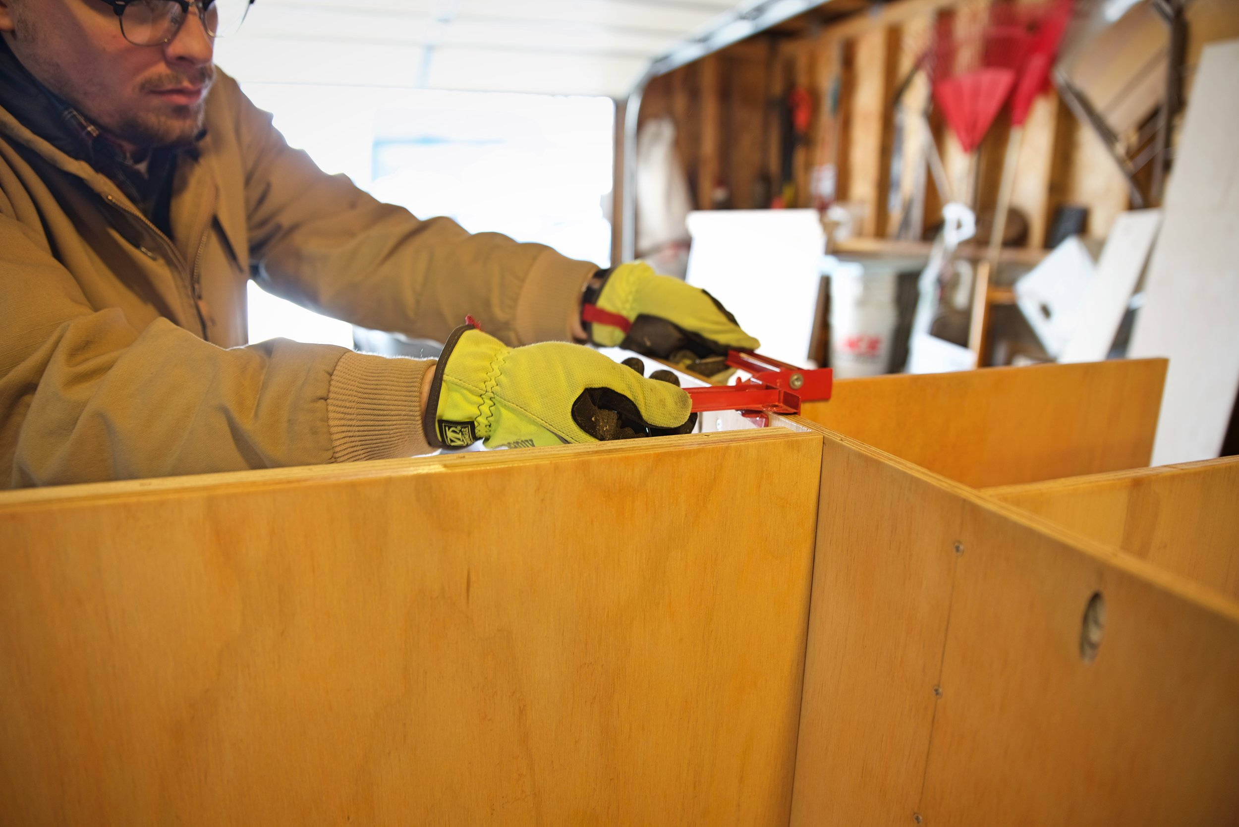 Ian removes a corner clamp after joining the chuck box shelf to the cabinet case.
