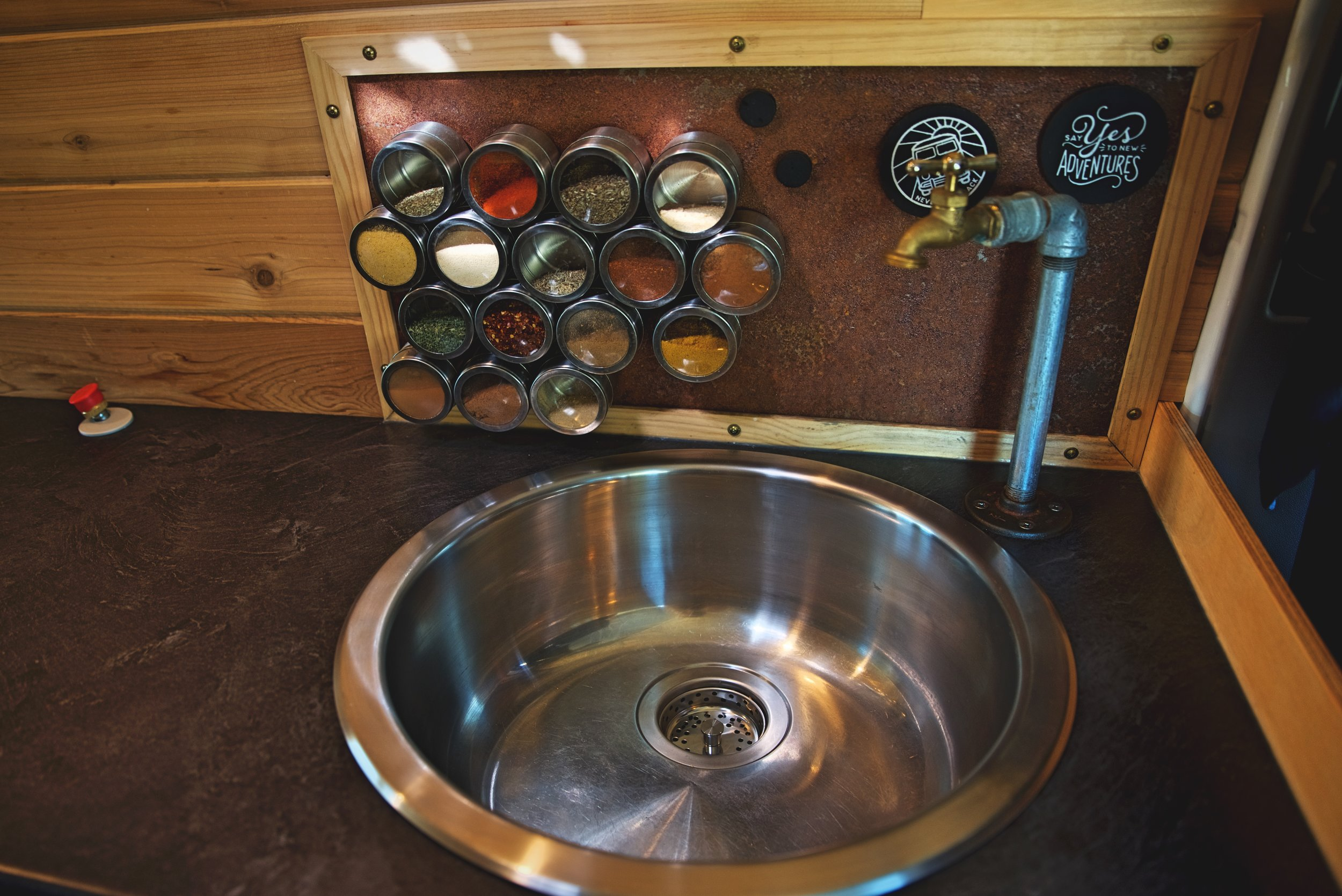 The sink is both an attractive and an extremely functional area of our van's kitchen. We keep our  magnetic spice tins  attached to our metal backsplash, which is a good way to keep them organized while living on the road.