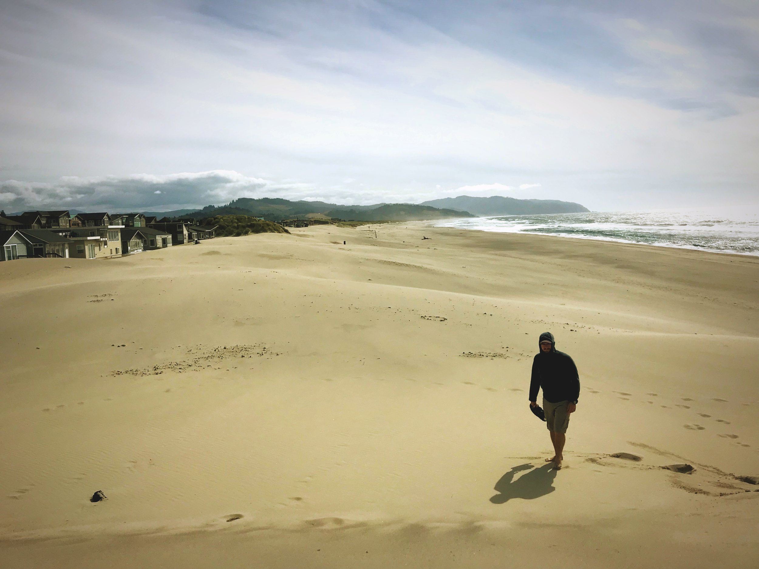 The sandy beach at Cape Kiwanda stretches on a long ways. The entire Oregon Coast is public land, so you can stroll as far as you want.