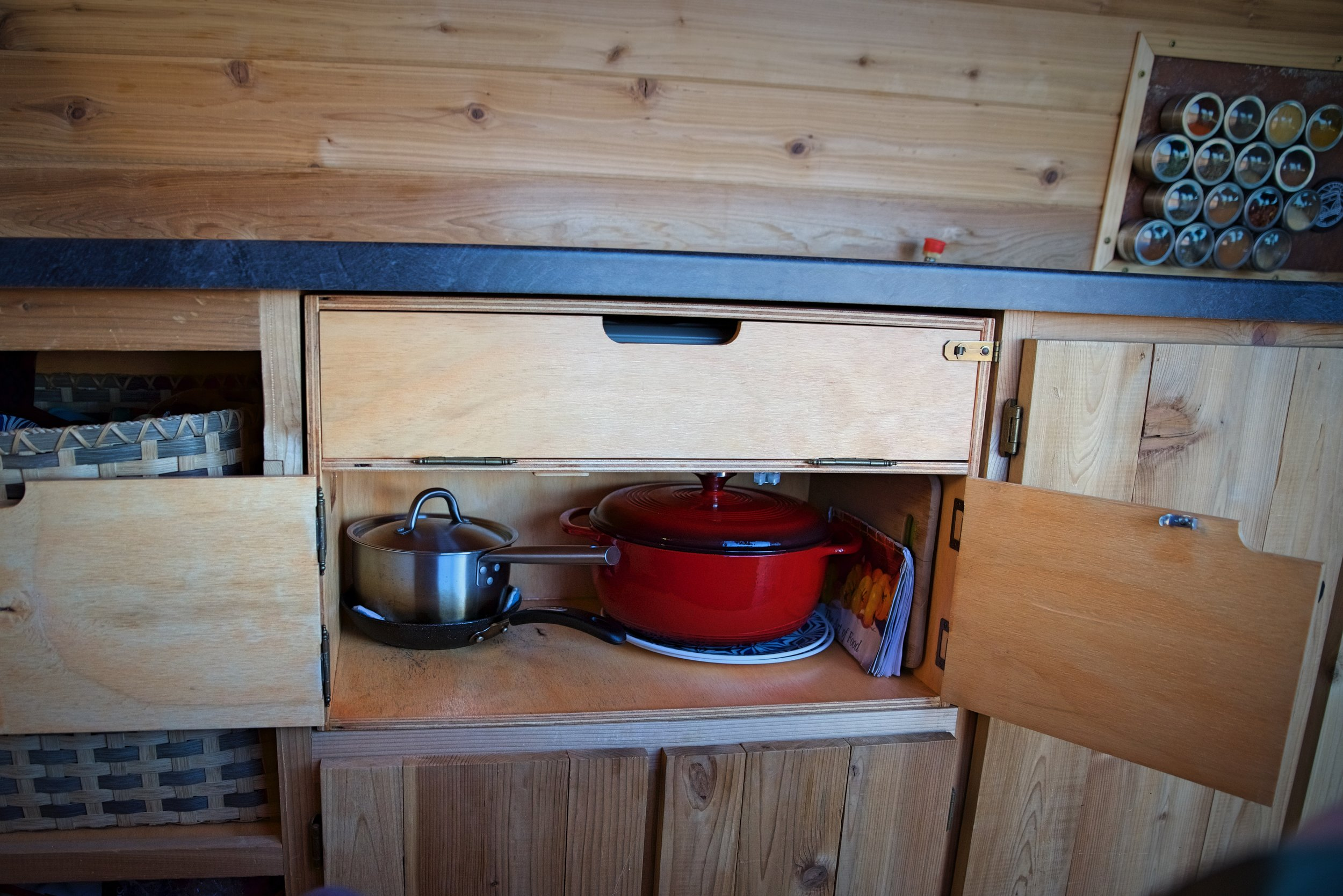 Our cabinetry includes a chuck box that we can remove in order to cook outside the van. It holds our dishes and our stove.