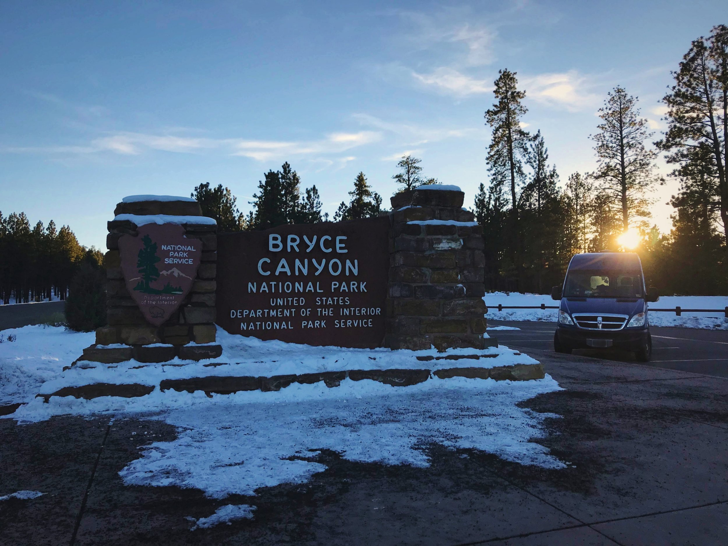 Our camper van parked by the entrance sign for Bryce Canyon National Park.