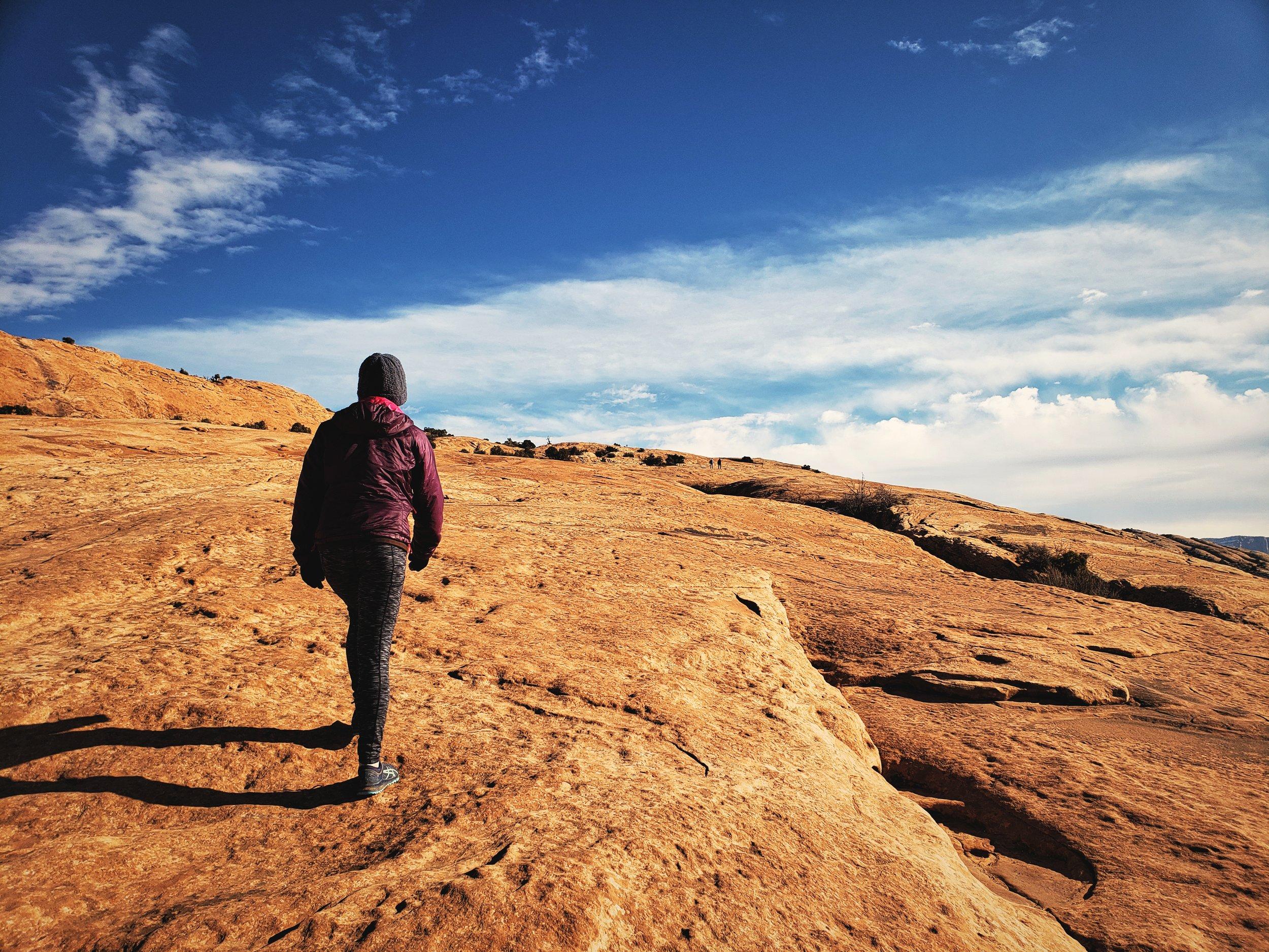 Climbing a massive, open slickrock slope to reach Delicate Arch.