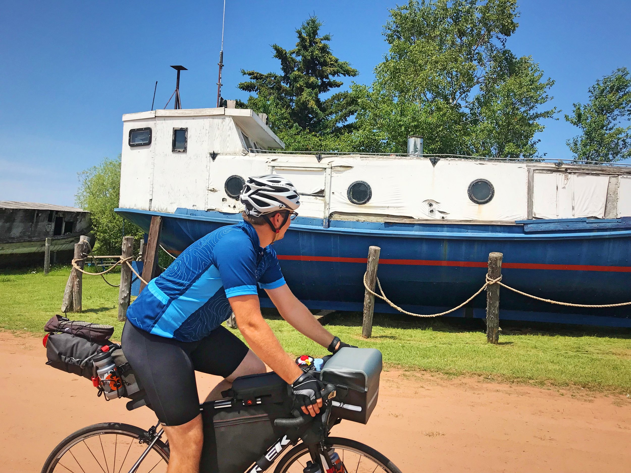 Ian bikes by his boat doppleganger near Corny Beach on our Lake Superior bike tour.