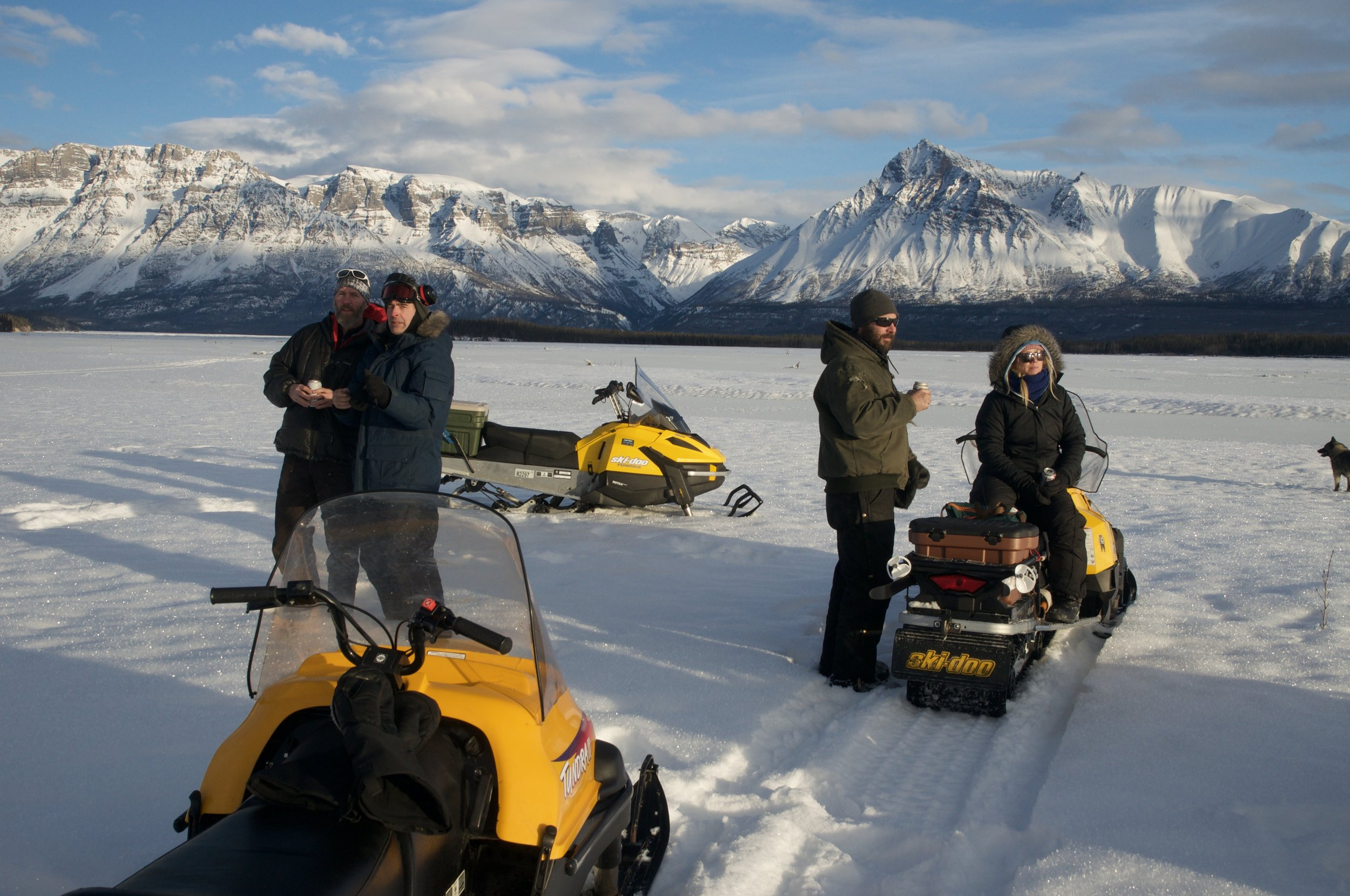 Malcolm Vance, Greg Runyan, Chris Chester and Julia Page stand on the Nizina River after a snow machine ride