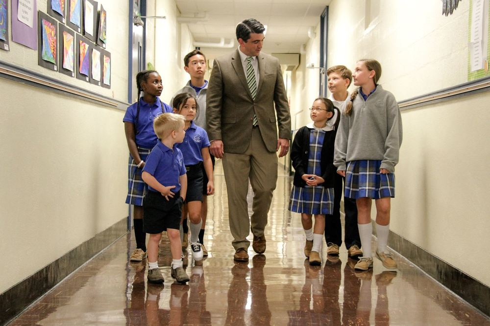 Principal Peter Rodgers walks with some students of Holy Rosary Catholic Academy.