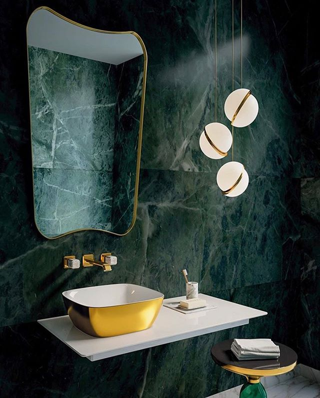 When a splash of gold, a jewel-like green, asymmetry and a floating light all come together so perfectly in a bathroom oozing with glamorous indulgence.  We love the gold basin. The beauty of that stool. The  curves of the mirror. The tone and texture of the tiles. And the light, of course. . Source: @prfirstlondon  Basin: @ceramicacatalano Lighting: @leebroom