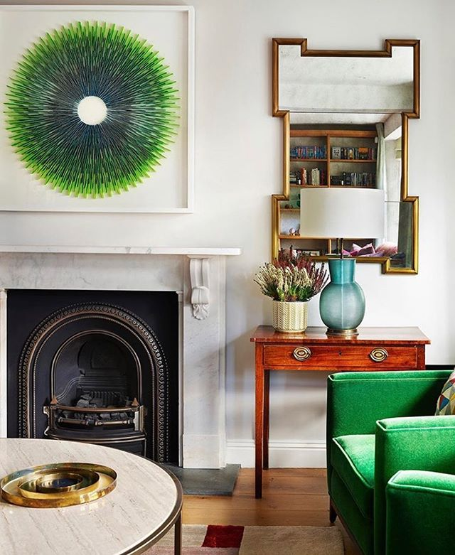 What stands out for you in this colourful bold interior? The glorious green in the statement art and matching armchair? The striking design  of the gold mirror? The fusion of shapes - curves, arches and  rectangles. The mix of contemporary pieces with antique brown. That fireplace? Or the gorgeous turquoise vase. Beautiful design from @stephenson_wright
