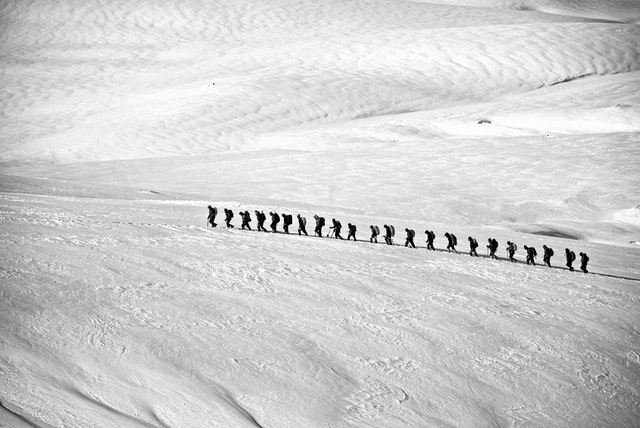 Imagery of a team of explorers walking together on a snow field - they'll get to their destination sometime.