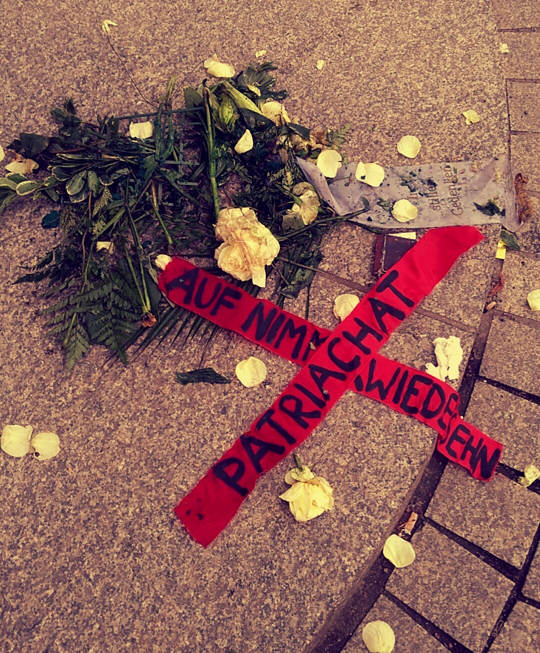 Destroyed flowers and banner reads: Auf Wiedersehen, Patriachat or Goodbye, Patriarchy.