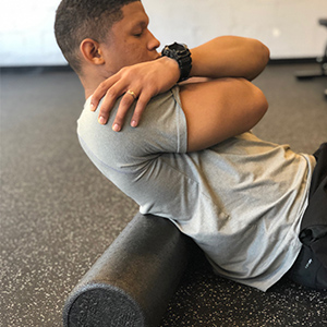 To begin rolling the back, place the foam roller at or above the bottom rib to avoid potentially injuring the lower back.