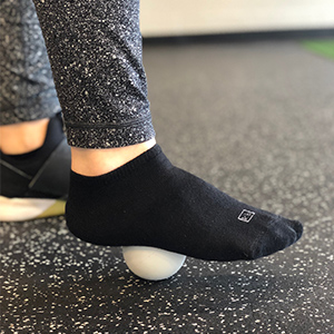 Start with the ball under the arch. Roll along the entire length of the foot, stopping to apply pressure at any trigger points.