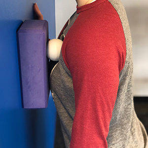 Target your pectoralis minor (chest) while standing facing the wall. Start with your arm down, and make minimal movement along the muscle grain.