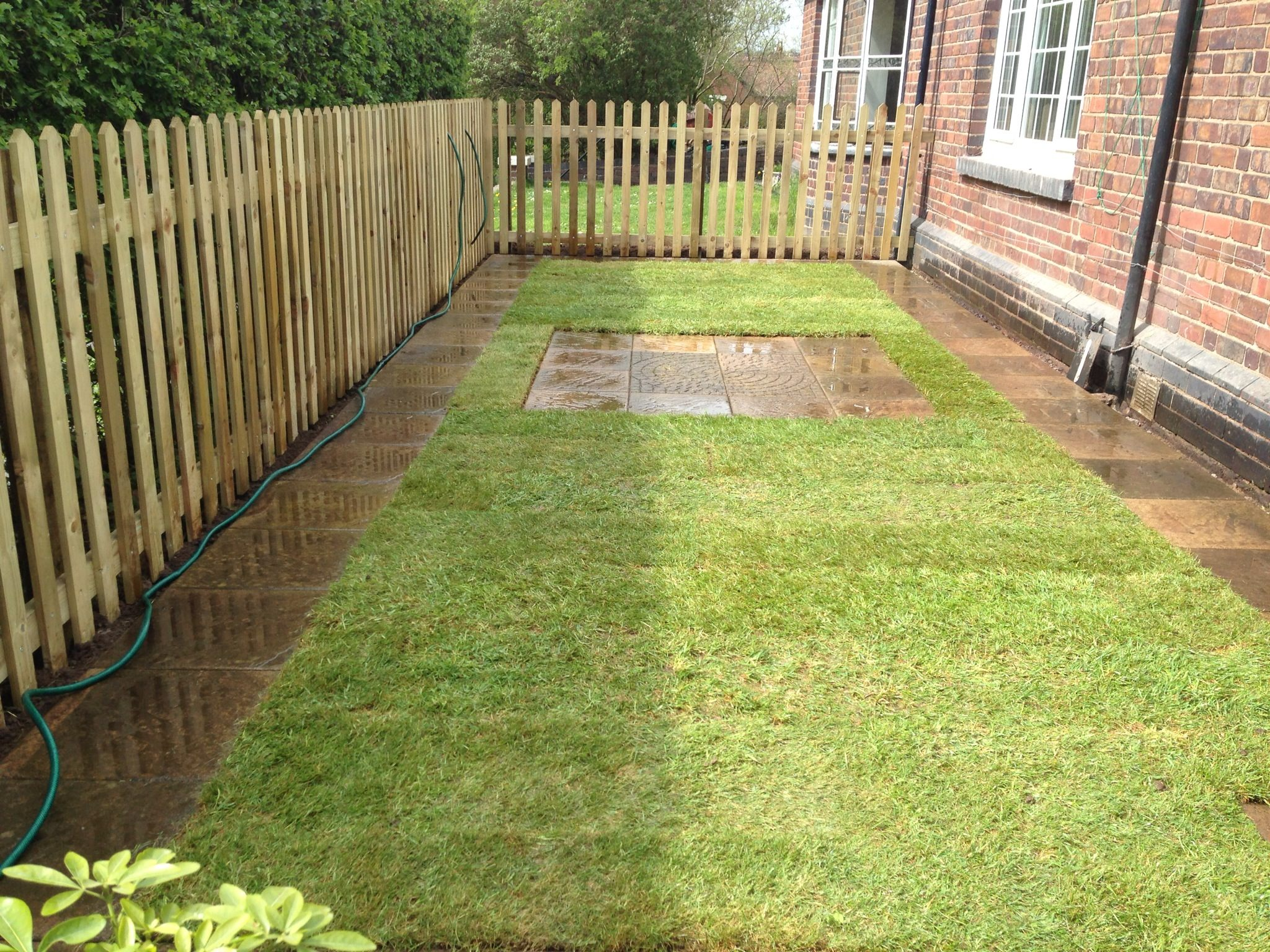 New lawn with picket fencing, small paved seating area and paved lawn edging