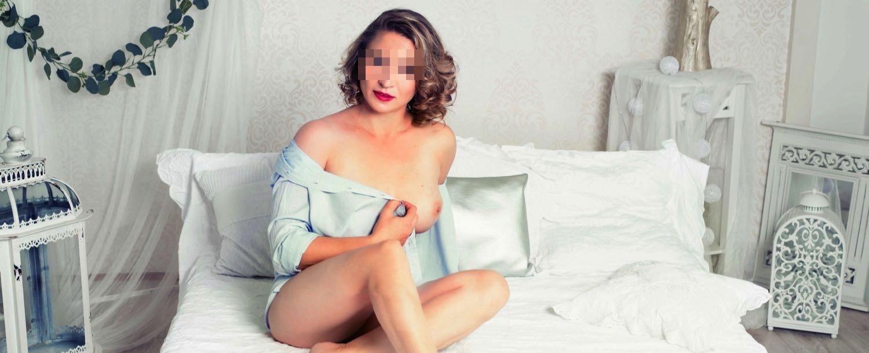 lady-amy-escort-hamburg-sitzt-aufrecht-auf-bett-mit weissen-laken-banner px.jpg