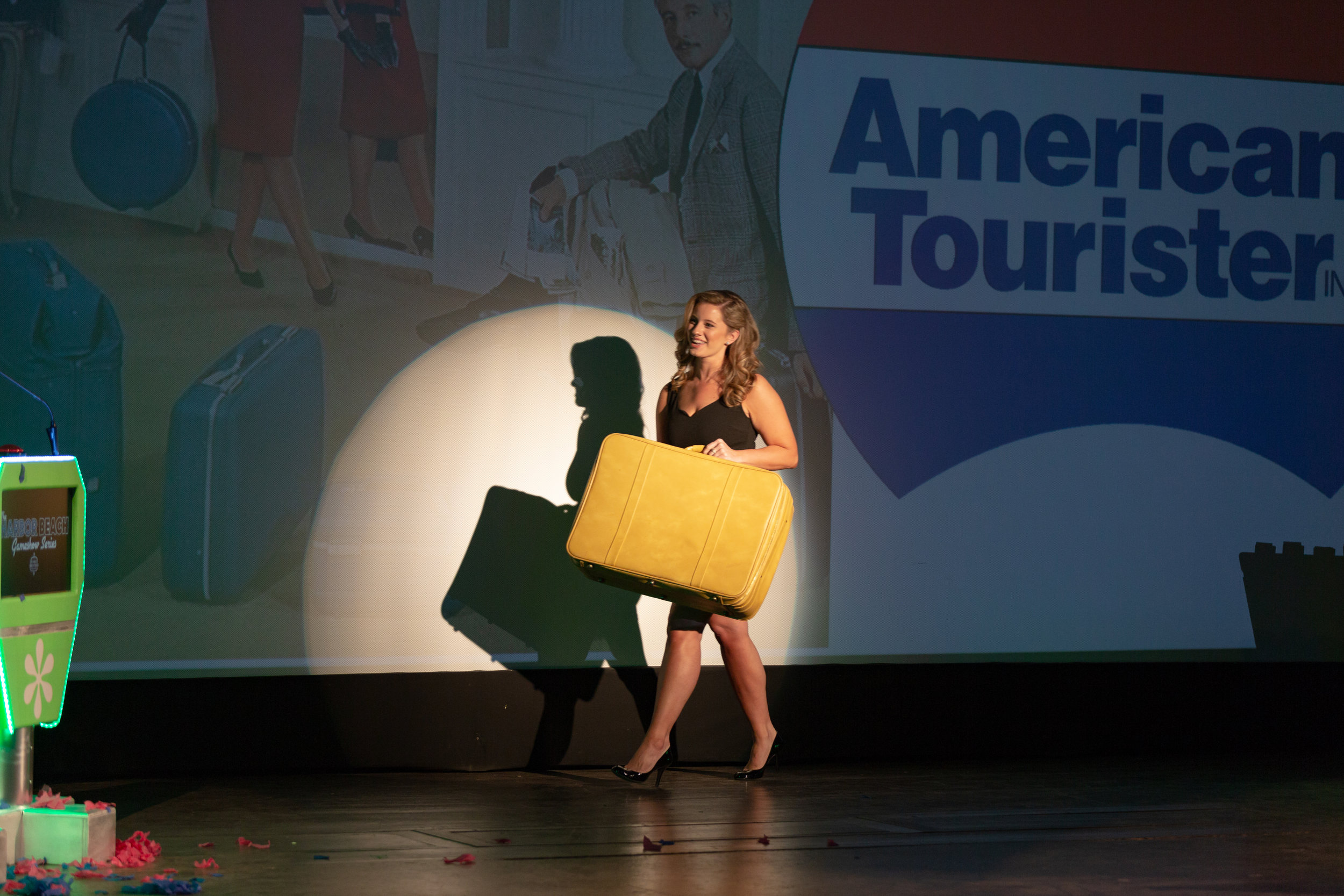 The Real Clark's Cutie, Rochelle Thompson delivers a authentic mustard yellow American Tourister luggage piece to a contestant.