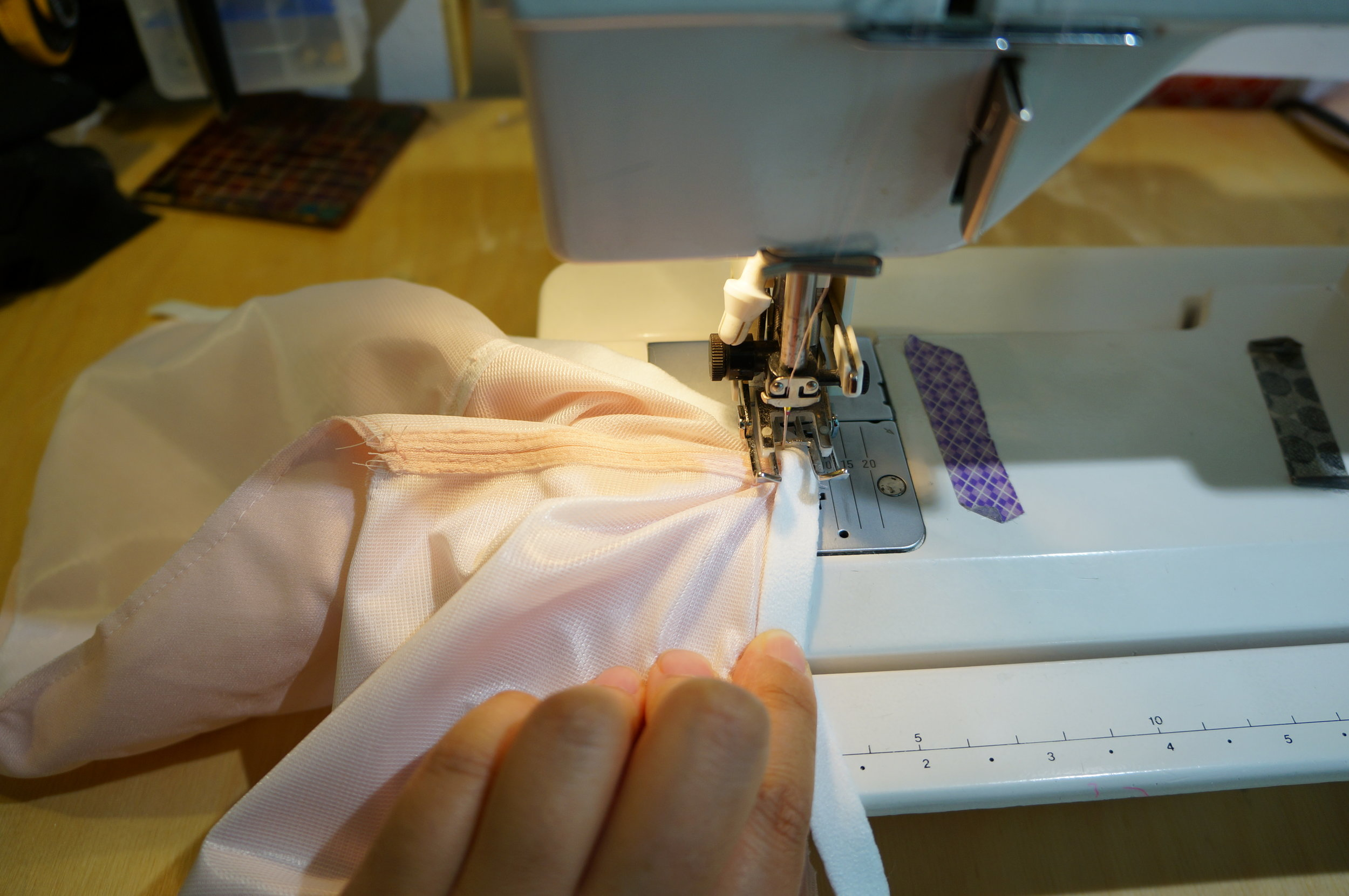 Stopped in the middle with needle down and presser foot up, rearrange fabric so second cup is smooth.