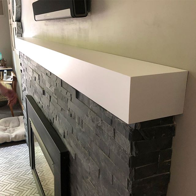 Fireplace mantle in a sleek minimalist design, painted crisp white.
