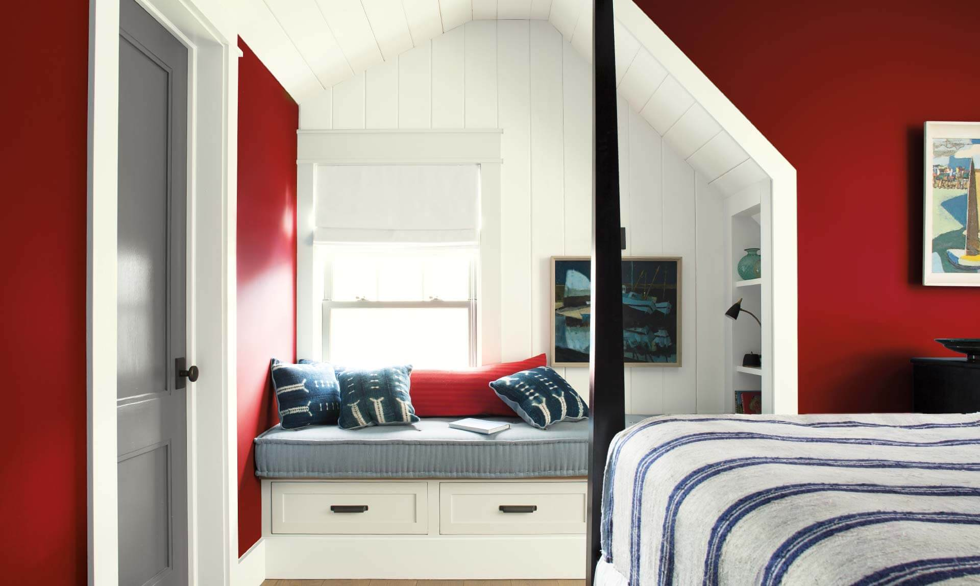 The power of red revs up warm weathered woods and misty ocean grass and greens of a serene seaside retreat