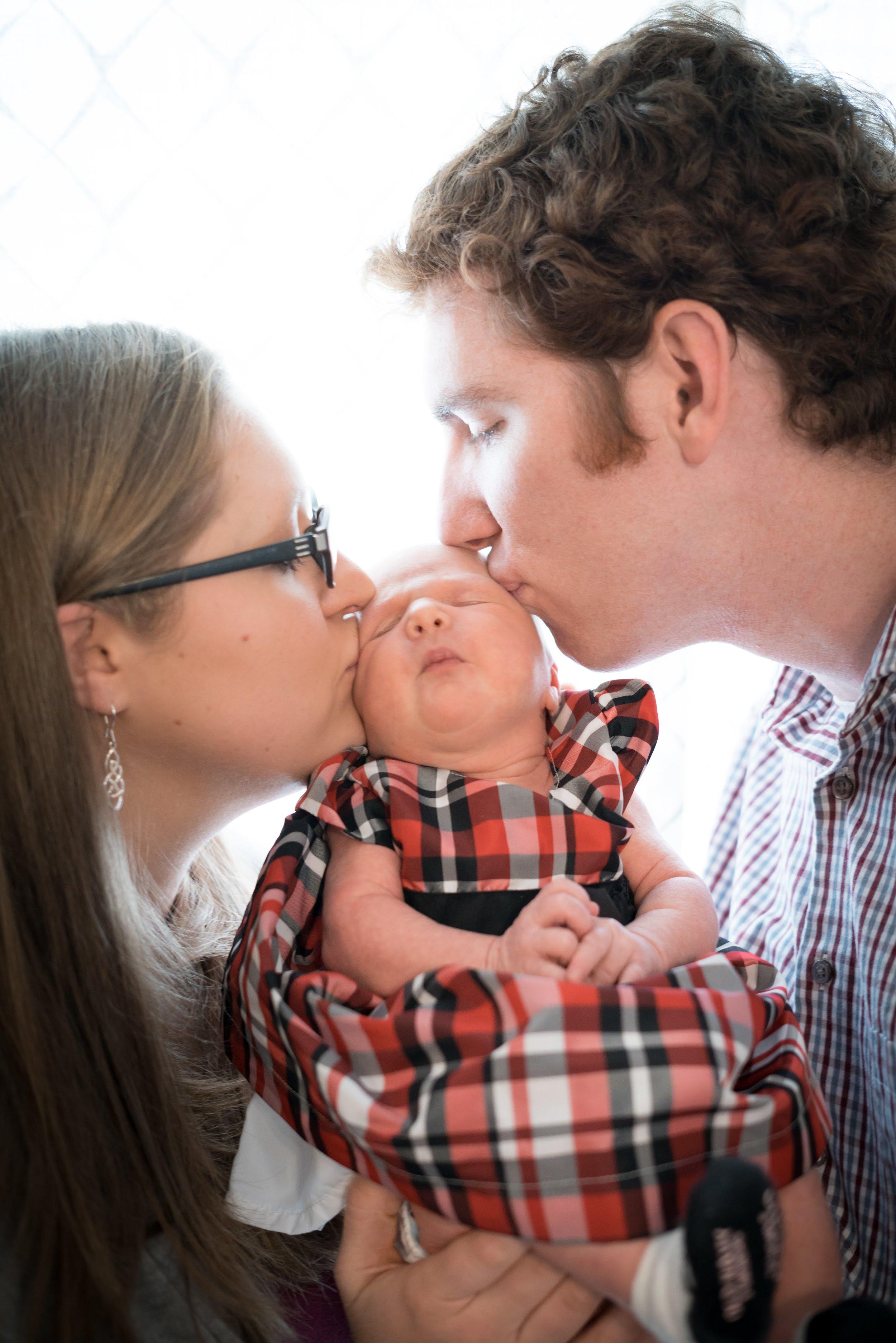 West parents kissing newbown