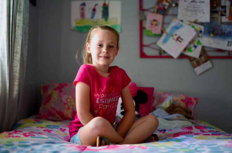 Gracie, 7, poses for a picture in her room. Gracie is transgender; she socially transitioned to a girl at the age of 4. (Lauren Hanussak/KQED)