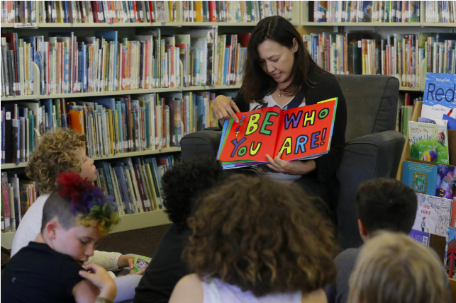 """In this Wednesday, July 12, 2017 photo, Sandra Collins, executive director and founder of enGender, reads a book to campers at the Bay Area Rainbow Day Camp in El Cerrito, Calif. Collins says, """"A lot of these kids have been bullied and had trauma at school. This is a world where none of that exists, and they're in the majority. That's a new experience for kids who are used to hiding and feeling small."""" (AP Photo/Jeff Chiu)  JEFF CHIU/AP"""