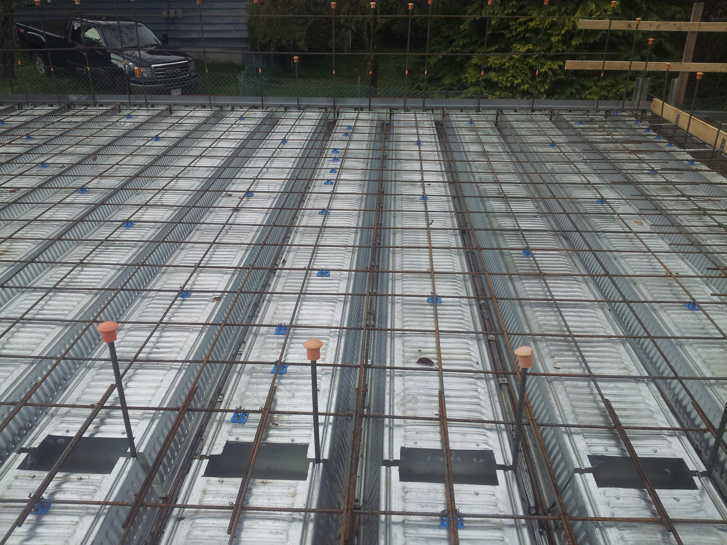 The Comslab floor system is then attached and poured to a 4 inch thickness in the field and 11 inches in the V beams