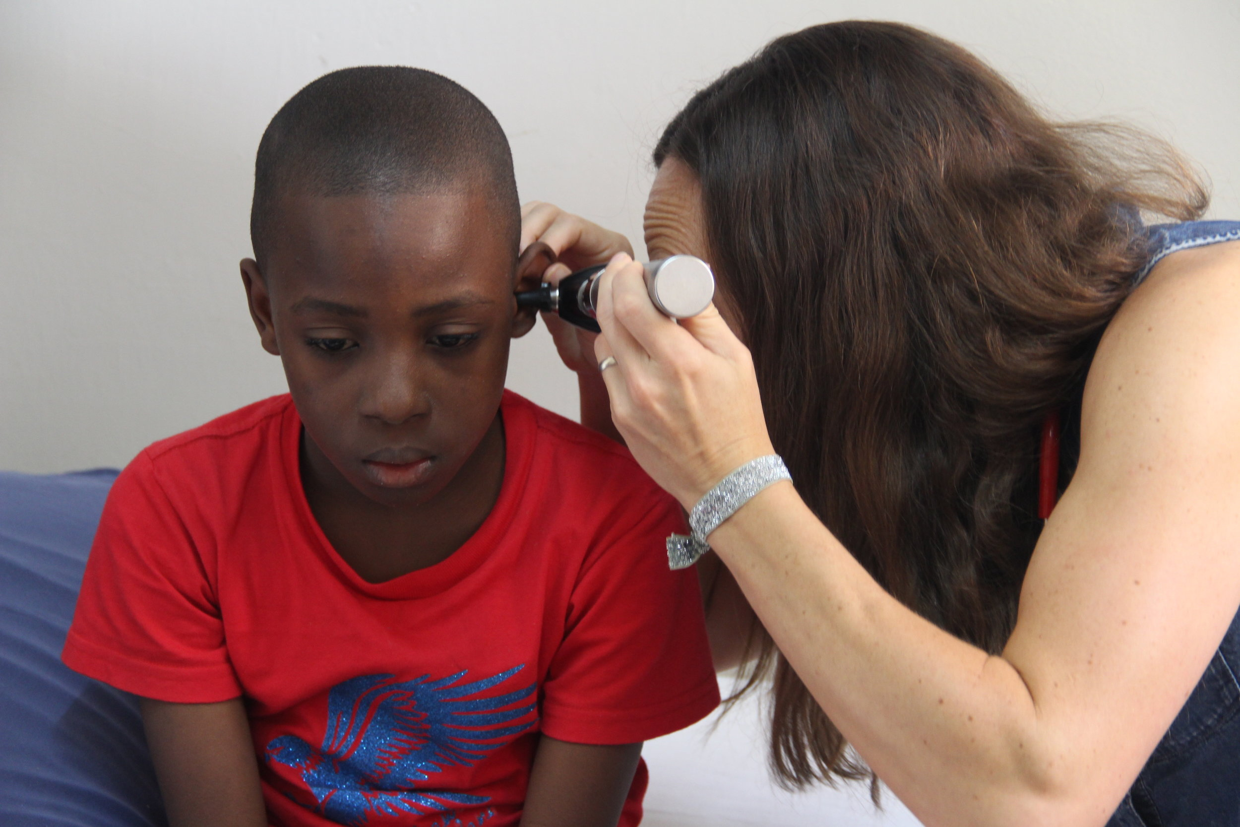 Dakar Academy's physician assistant, Mrs. Lindsay Musser, uses her otoscope to examine a student.