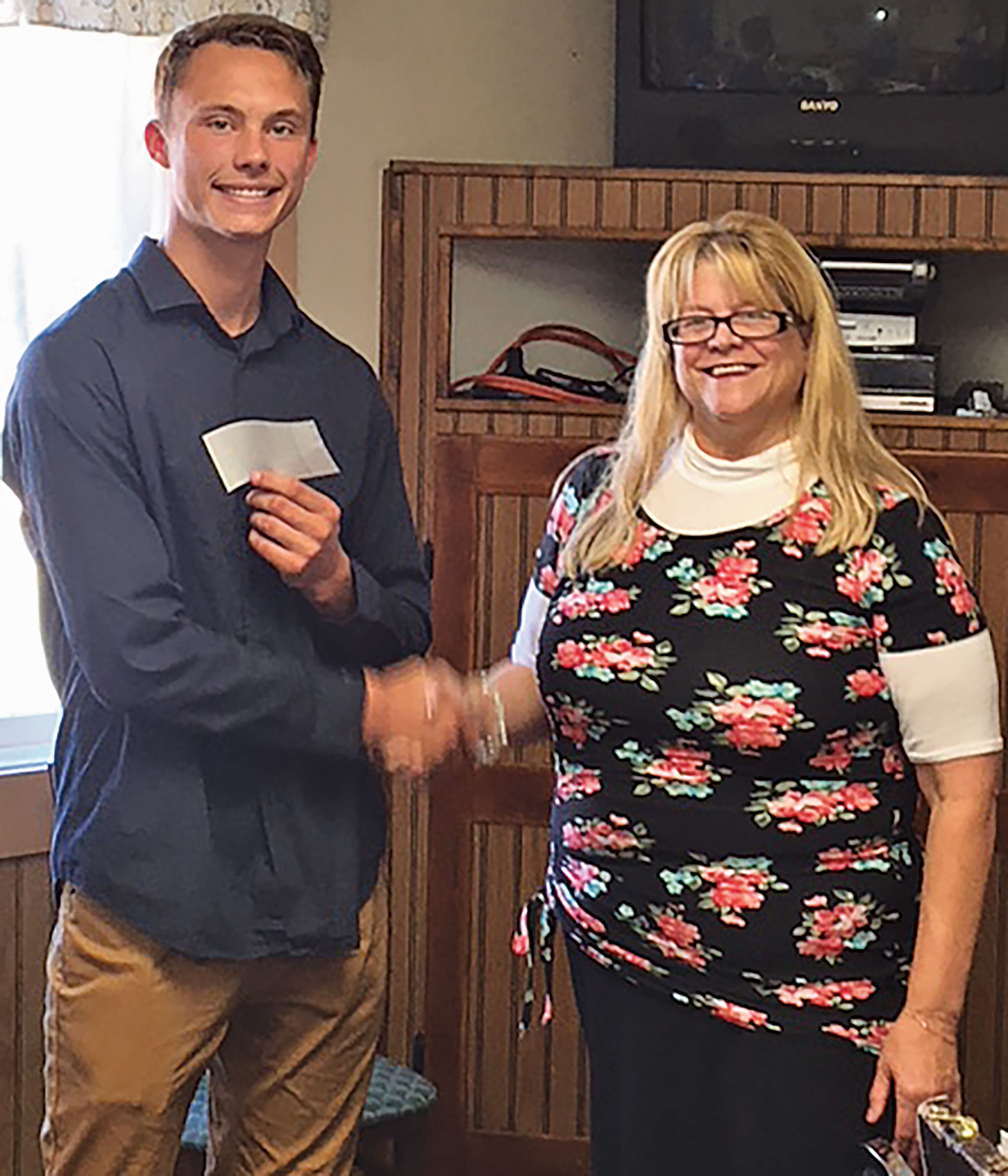"""- Custer Rotary Club president Jill Kettle presents a $350 check to Custer senior Nathaniel Youngblood. The money will be used to buy T-shirts for Youngblood's """"Cats on the Run"""" senior project involving more than 70 elementary students."""