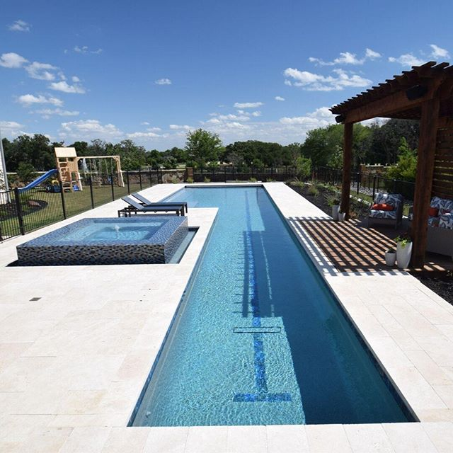This client requested a sports pool that is long enough to double as a swim lane. To match the contemporary design of the home was not an issue with the straight-line nature of the project. The client also requested that this pool be heated for winter swimming, and with that in mind we added an automated pool cover system to this project to help maintain a warm pool in the fall and winter months, while adding the benefit of a clean pool year-round. This project was rounded out with an attached 360-degree spillover spa and a fire pit for relaxing.  A heated pool for the winter  Designers: Travis Berry + Charlie Claffey Project Manager: Brent Schumacher