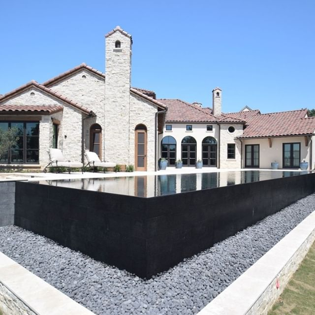 A lot with an elevation change was the perfect canvas for this perimeter overflow pool.  The black bottom and dark tile help turn this pool into a reflecting pool with tranquility in mind.  The client has small children and they were concerned with not being able to view the catch basin behind the pool. To alleviate this concern, we suspended a grate over the basin and then covered the grate with river rock. Truly a contemporary classic!  Designer: Charlie Claffey Project Manager: Brent Schumacher