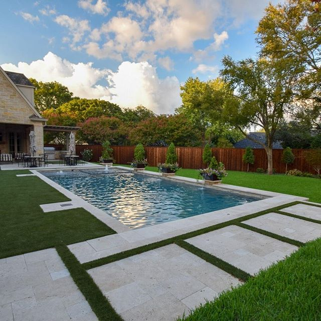 """Safety and beauty required for this French styled home resulted in a automatic cover.  Understated elegance was achieved with water and planting copper bowls for the focal points but still keeping the view open to the landscape behind the pool.  The slope of the existing yard was handled by the pool wall as the retaining wall.  Not changing the remaining yard grade kept the trees from being killed.  The cap was 24"""" wide to support the bowls and minimize joints with the Travertine coping.  The pool perimeter tile matches the home stone color tones and the spa and cover dam wall tile matches the water color.  The synthetic grass gives more gardenesque feel and keeps clean look .  Travertine patios flanked both ends with steps down to rest of yard.  The walk on lids for cover were also done in the Travertine.  Looking out of the home everyday you have a beautiful view but when the Grandkids come you have a safe place as well.  Designer: Mike Farley Project Manager: Bobby Brzozowski"""