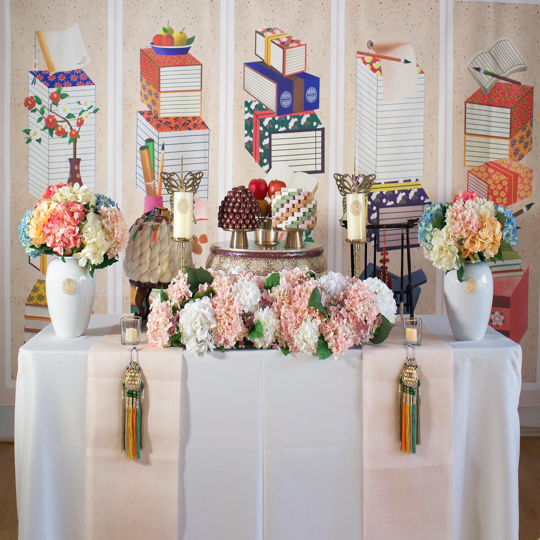 책가도 1단(Book Theme #1) - Included: Book Theme backdrop, 1 pearl small table, linen runner, 4 high quality brass plates, 2 butterfly brass candle holders, display rice cakes, dates, fruits, centerpiece, 2 flower vases, display mini flowers, premium brush rack, traditional ornaments, shil ta rae, wood small table, 2 mini candles책가도 1단 상품구성 : 현수막, 모시러너, 자개상 1개, 꽃과 촛병 2개, 중앙꽃, 실타래, 나무소반, 모형 삼색한과, 대추, 과일들, 유기 나비촛대 2개, 방짜유기 4개, 상화, 노리개,프리미엄 붓걸이, 데코초 2개