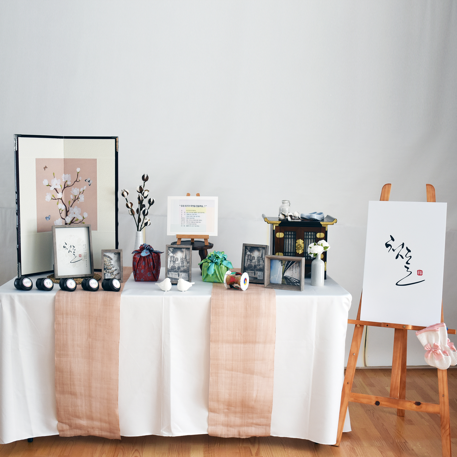 Traditional photo table #1 - Included: Mini traditional folding screen, 4 picture frames(5x7), 1 picture frames(4x6), traditional phone table, traditional rubber shoes, mini janggu, 2 traditional wrapping boxes, 6 Doljabi traditional jars, 2 birds, mini wooden table, flowers and vase, easel, first birthday board, traditional socks.상품구성: 미니병풍, 액자 5x7 4개, 액자 4x6 1개, 전통 창살 전화대, 고무신, 미니장구, 선물보자기 2개, 돌잡이 항아리6개, 모시 러너, 사랑새, 개다리 소반, 장식꽃, 목화와 꽃병, 이젤, 첫돌 보드, 버선