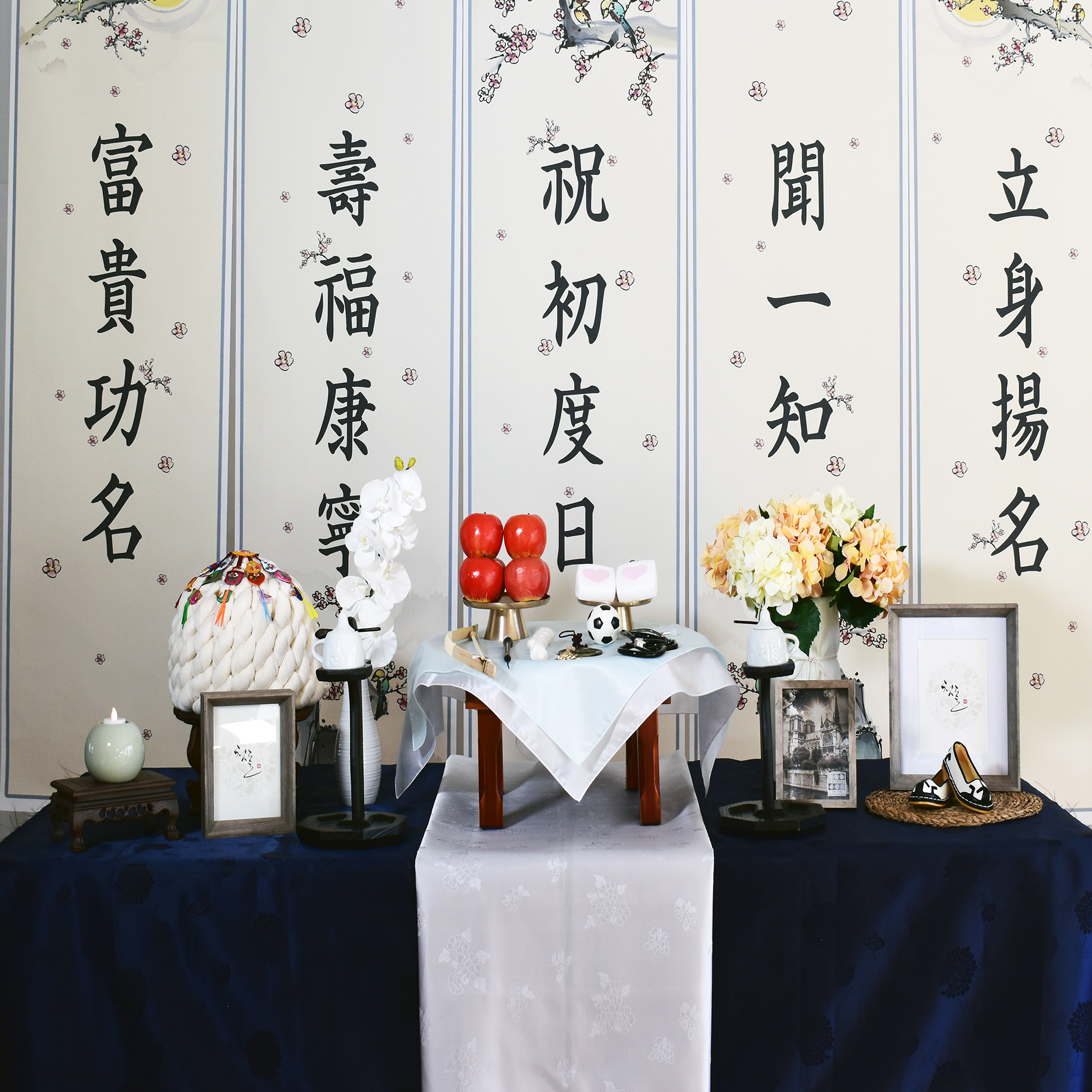PETIT STYLE TABLE RENTAL: 축초도일 (The First Time-Navy) - Included: The First Time backdrop, round wooden table, traditional tablecloth, traditional runner, small tablecloth, 2 kerosene lamps, 1 mini wooden square table, traditional candle holder, display apples, rice cakes, silk flowers and plastic vases, shil ta rae, traditional accessories are randomly picked, 3 picture frame (5x7), Doljabi Items (Pick 5 items- Ma-pae, coin, stethoscope, writing brush, soccer ball, thread, bow and arrow)** Mix &Match backdrops and runners (choose from traditional table)*** Pick up- Everything included in the picture except display rice cakes, display fruits, brass plates.* Out of state - mini wooden table, display rice cakes, apples are not included. (optional) Will change to 2 small picture frames. All accessories are randomly picked.* Shipping fee will apply. Fees might vary depending on location.상품구성: 현수막, 상 1개, 고급 한복 원단 테이블보, 한복 원단 러너,상보, 호롱불 촛대 2개, 호롱불 2개,전통 사각 소반 1개, 전통 촛대 1개, 모형 사과, 백설기, 꽃과 아크릴 화병 2개, 상화, 실타래, 전통 장식품들 램덤, 액자 3개 (5x7), 돌잡이 용품(5개 선택 - 활, 실, 엽전,붓, 마패, 축구공, 청진기),** Traditional Table 에서 현수막, 러너 Mix & Match 하실수 있습니다.*** Pick up- 사진에 모든 물품 포함되지만 모형떡, 과일, 유기그릇은 포함되지 않습니다. 전통 소품들은 랜덤입니다.* 타주시 - 깨지지 않는 소품들로 나갑니다. 작은 액자 2개로 변경, 유기그릇, 개다리 소반은 포함되지 않으며, 모형 과일, 떡은 옵션입니다. 전통 장식품들은 랜덤입니다.*배송시 배송비는 추가이며, 지역따라 배송비가 다를수 있습니다.